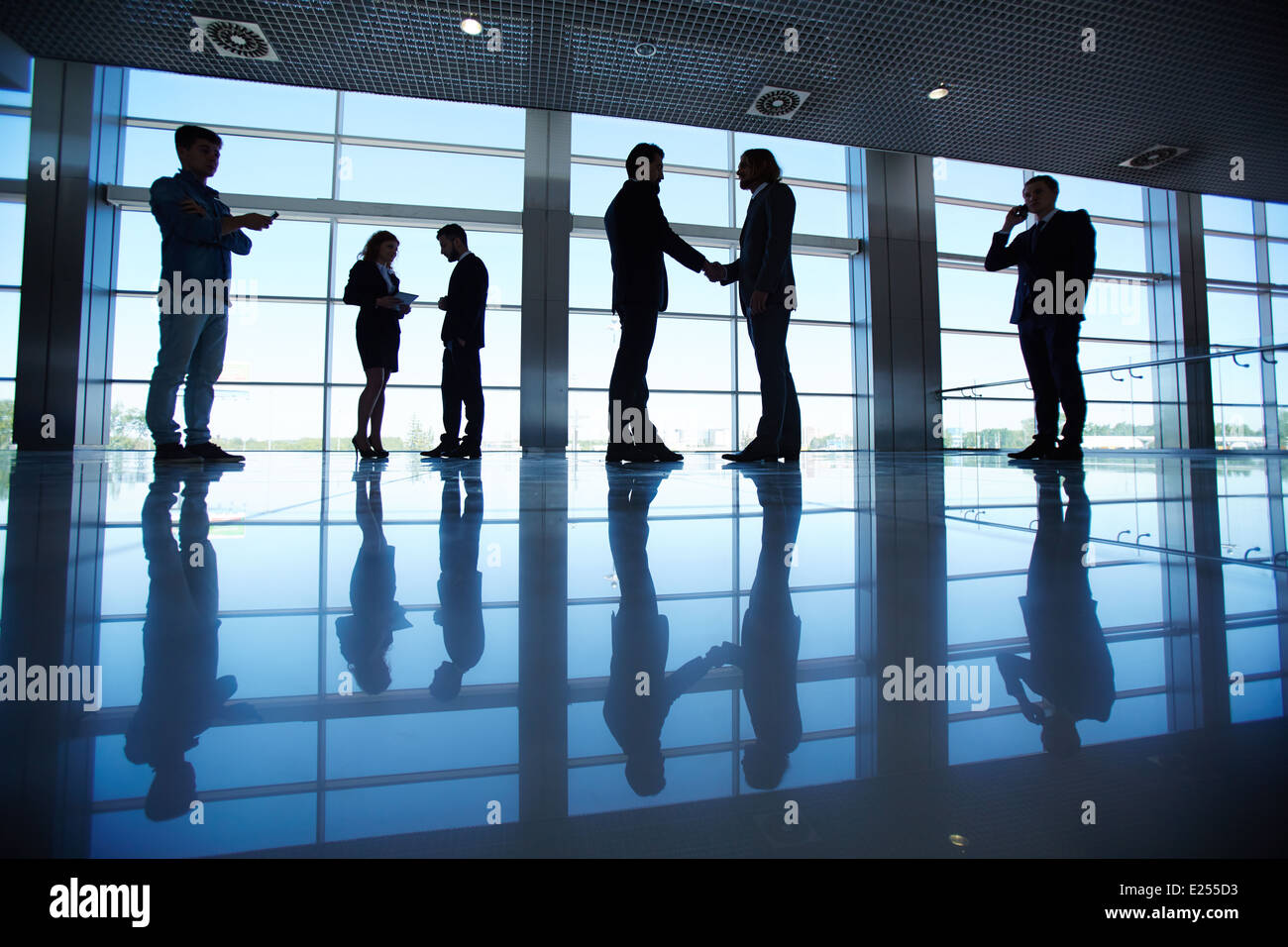 Silhouettes of several office workers working in office - Stock Image