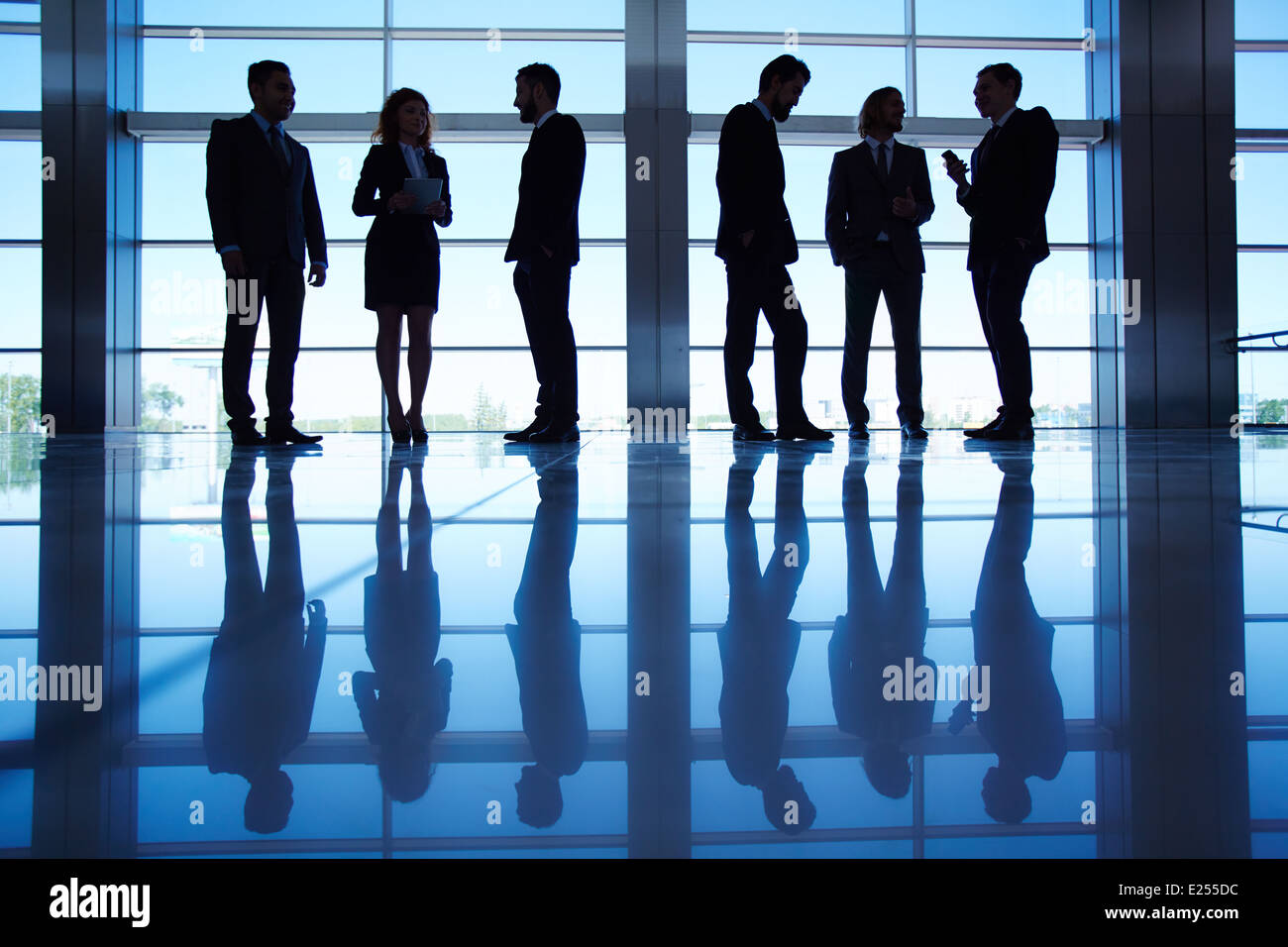 Silhouettes of several office workers standing by the window and working - Stock Image