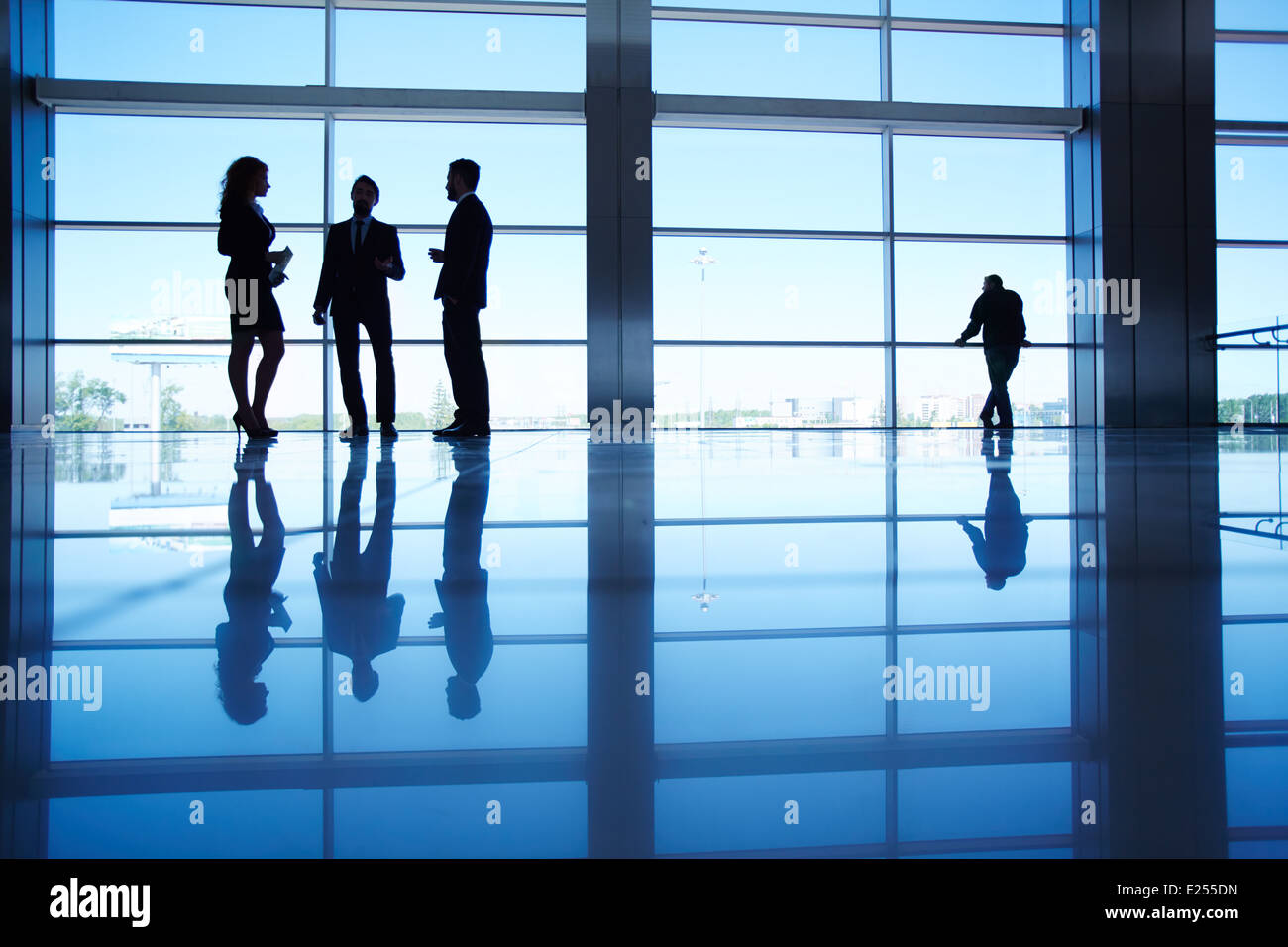 Silhouettes of several office workers standing by the window and talking - Stock Image
