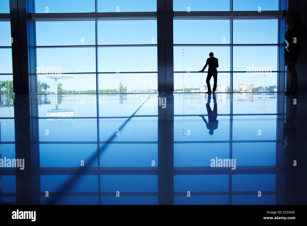Outline of white collar worker standing by the window of office - Stock Image