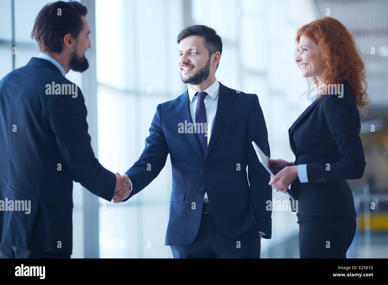 Two businessmen handshaking after striking grand deal - Stock Image