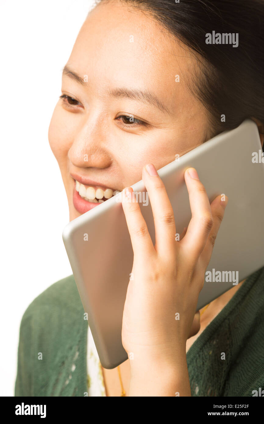 Asian woman with a large cellphone on white background - Stock Image