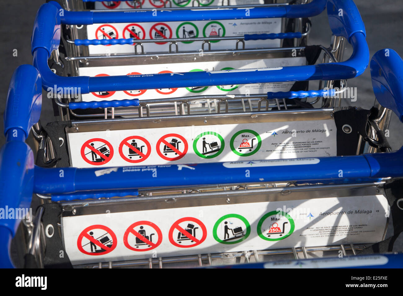 Close up of line of stacked luggage trolleys with rules about use, Malaga airport, Spain - Stock Image