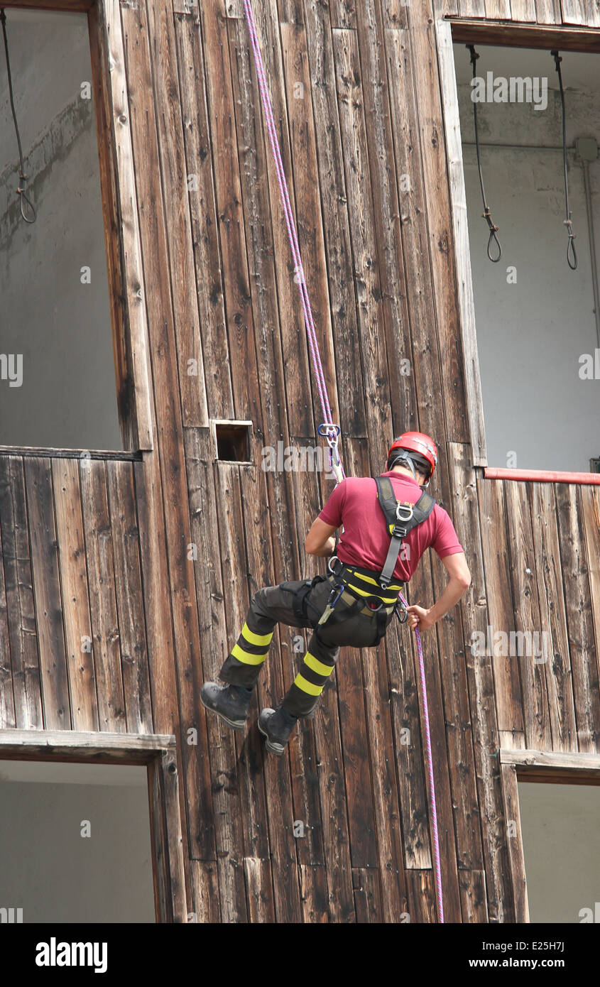 brave fireman climber expert you haul in the wall of the House abseiling during an exercise - Stock Image