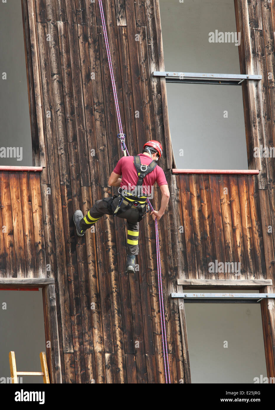 expert firefighter climber down into the wall of the House - Stock Image