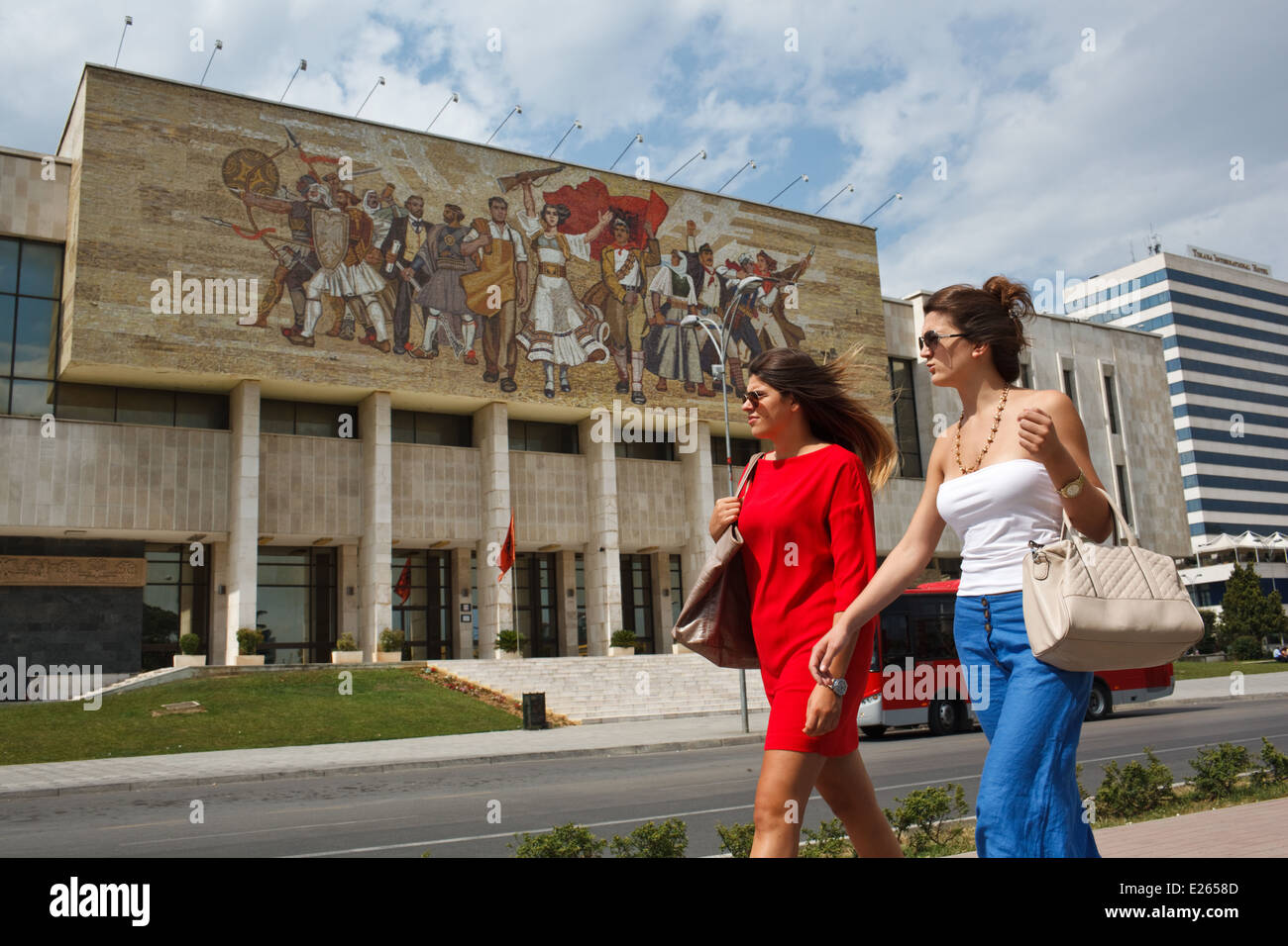 Two young fashionable women walk past National Historical Museum at Skanderbeg Square, Tirana, Albania. - Stock Image