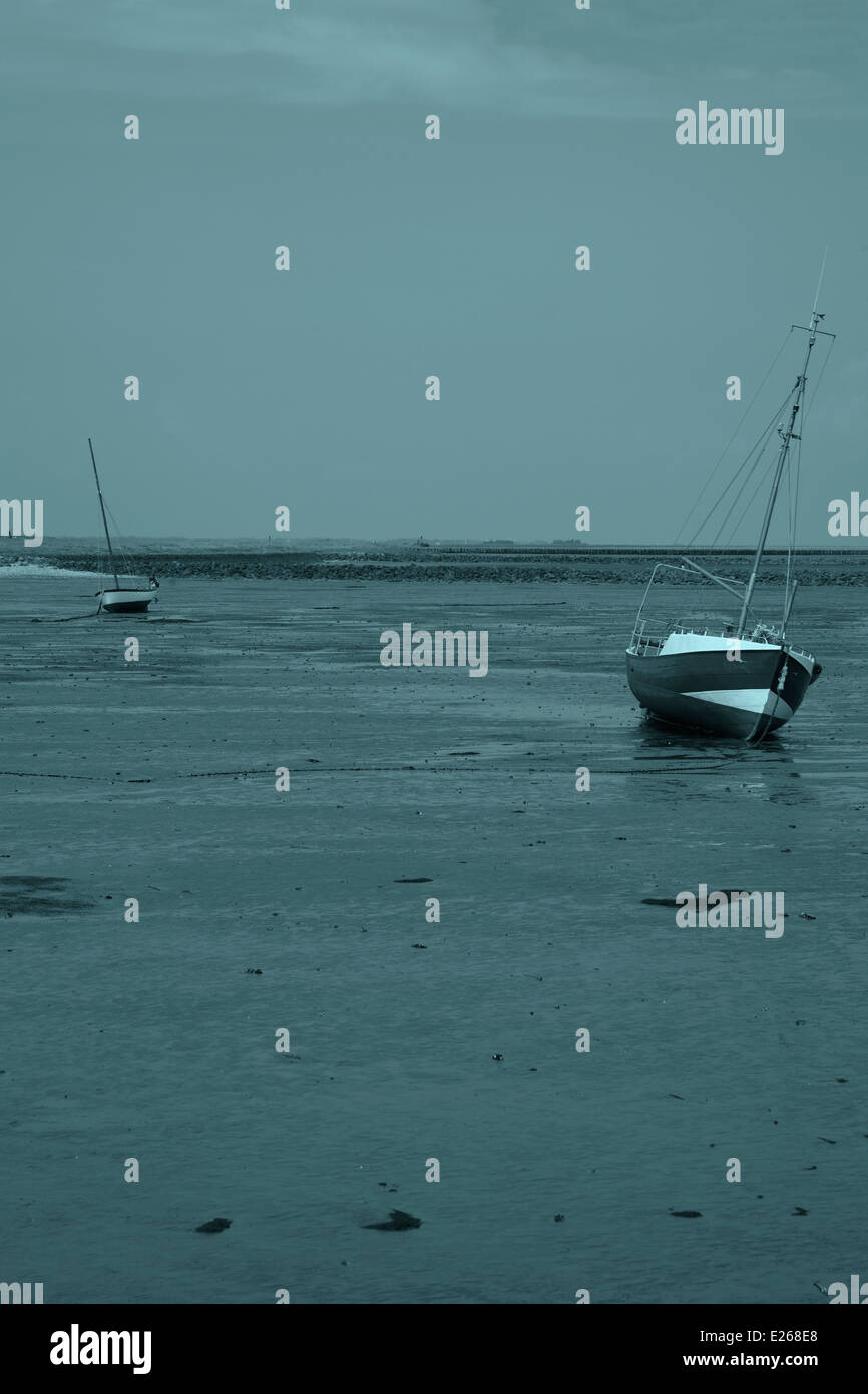 Two boats lying on the Watt  at low tide in the worldheritage waddensea around the Hallig Hooge. - Stock Image