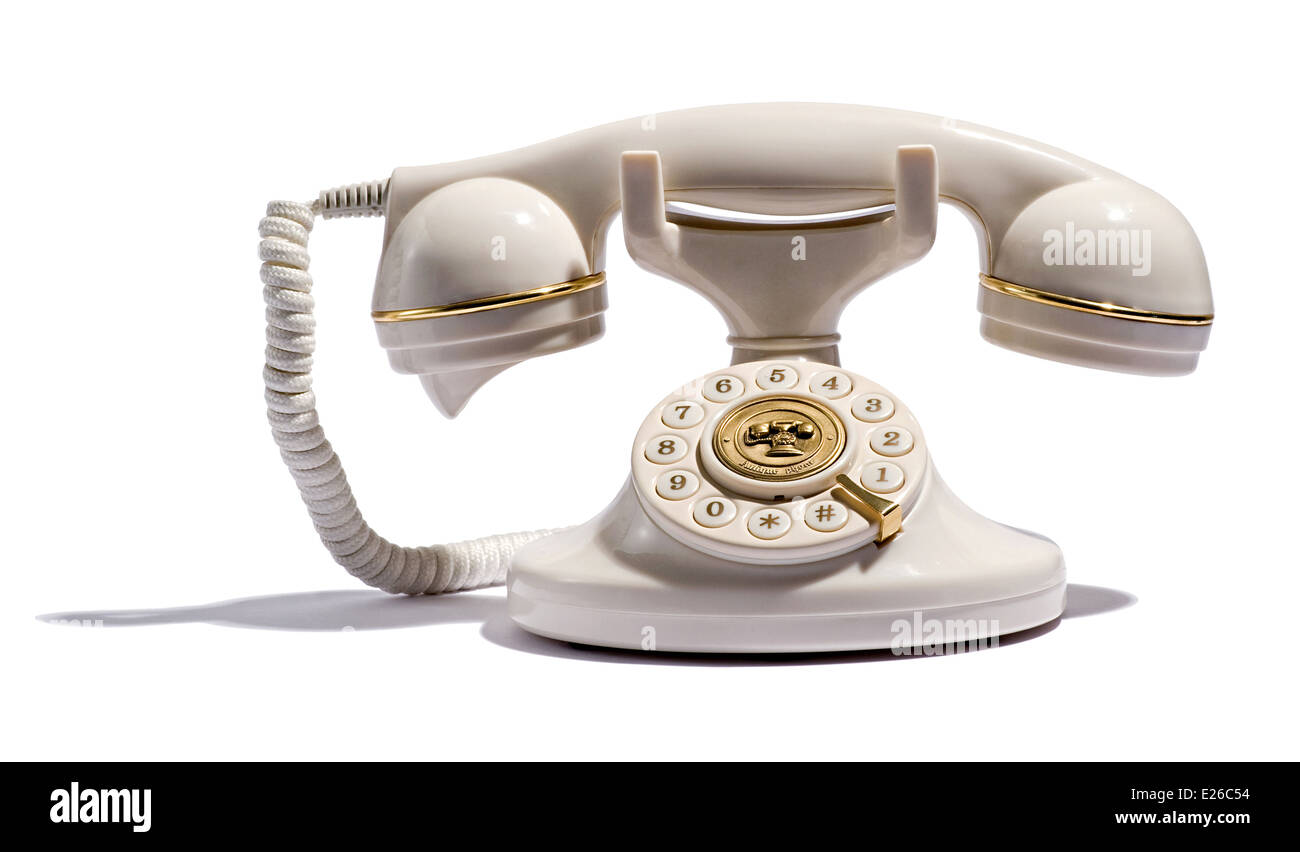 Old retro telephone with a handset and numbered dial on a white background - Stock Image