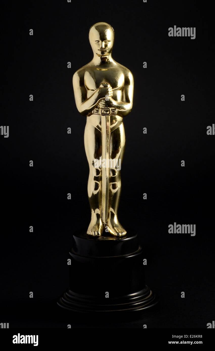 Golden replica of an Oscar film award on a black background - Stock Image