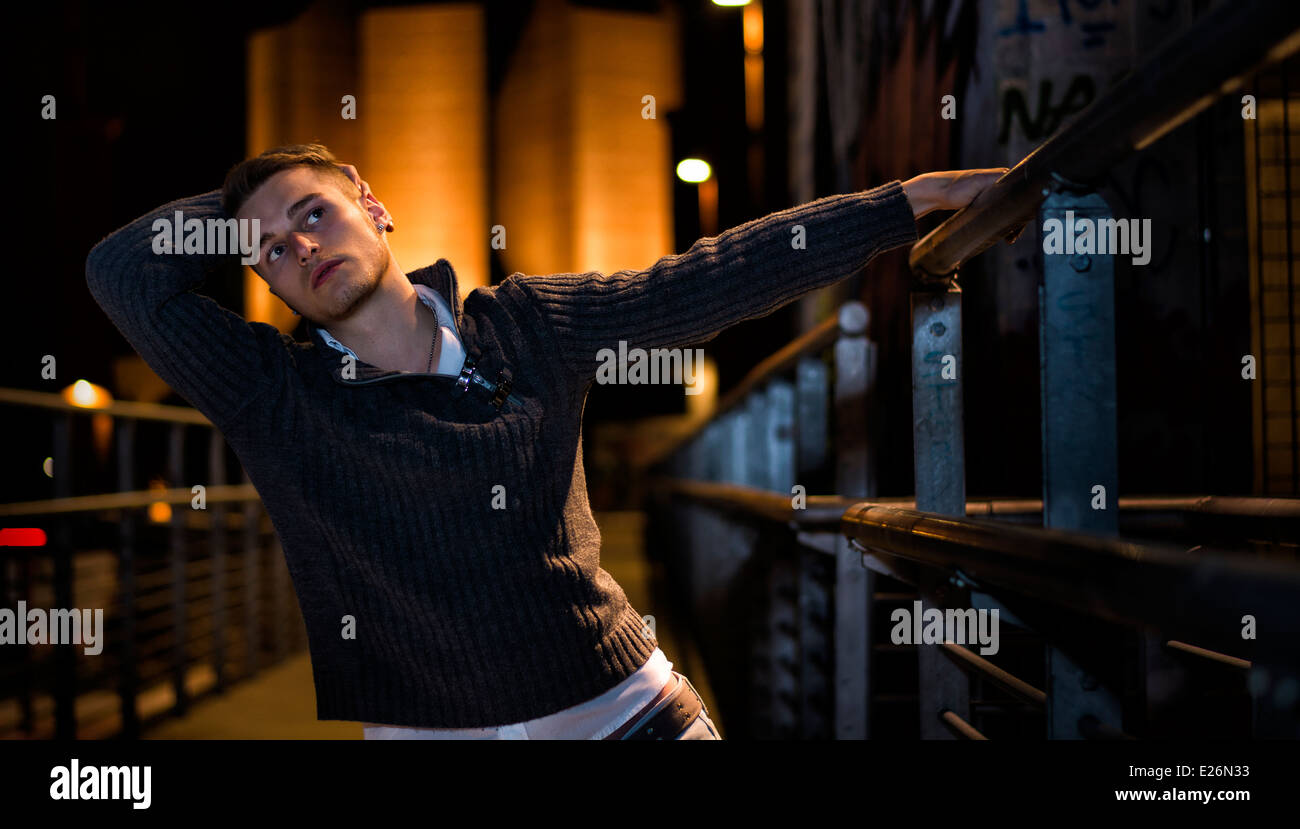 Handsome blond young man alone in urban setting, hanging from handrail, night shot - Stock Image