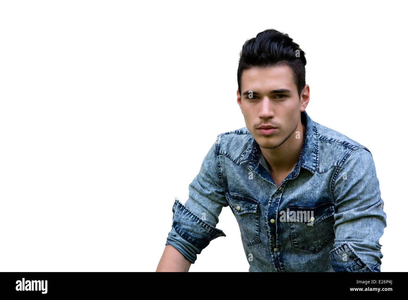 Handsome black haired young man in denim shirt isolated on white background - Stock Image