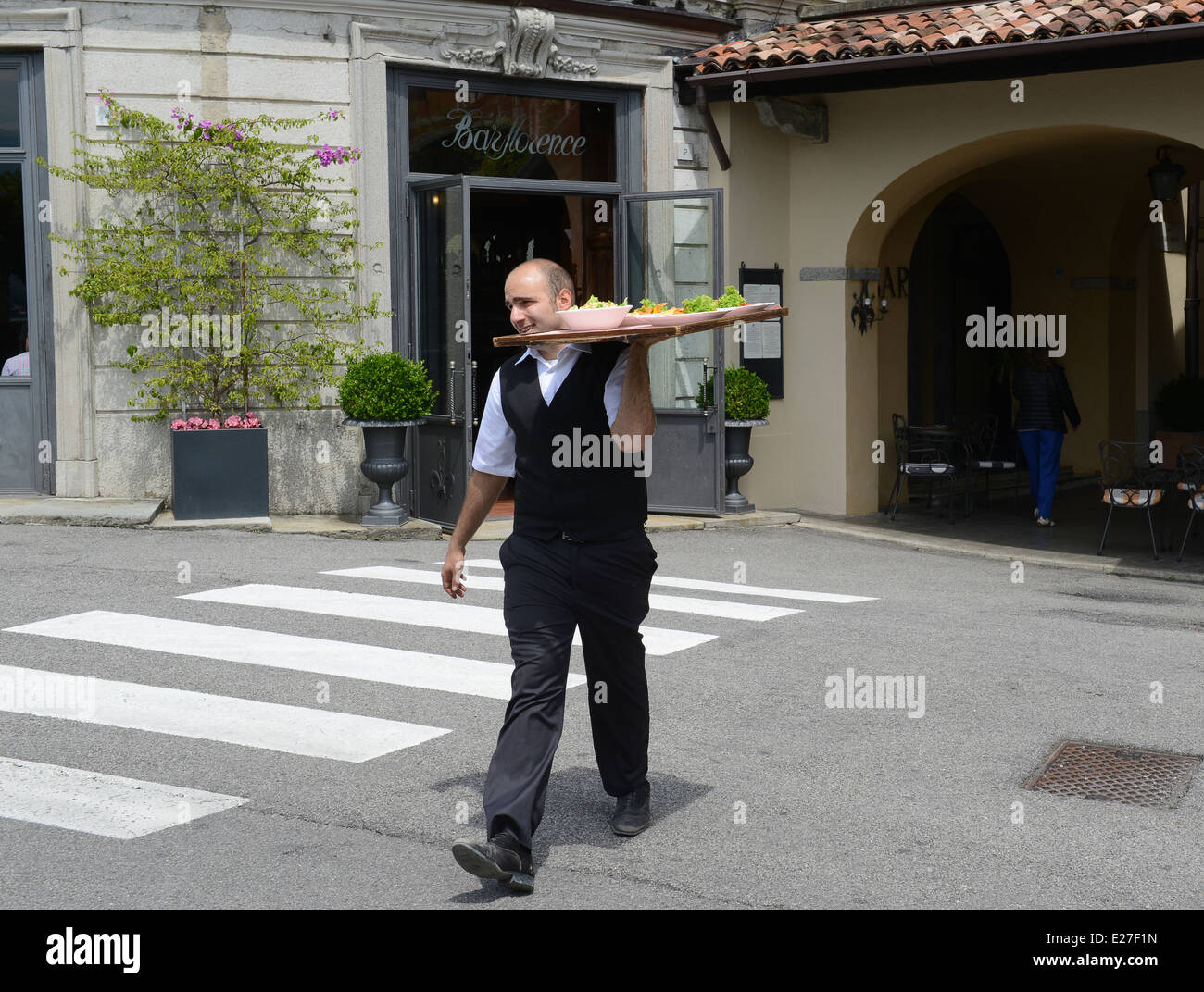 Italian waiter crossing road with food tray Bellagio on Lake Como Italy / waiters service Italian restaurant - Stock Image