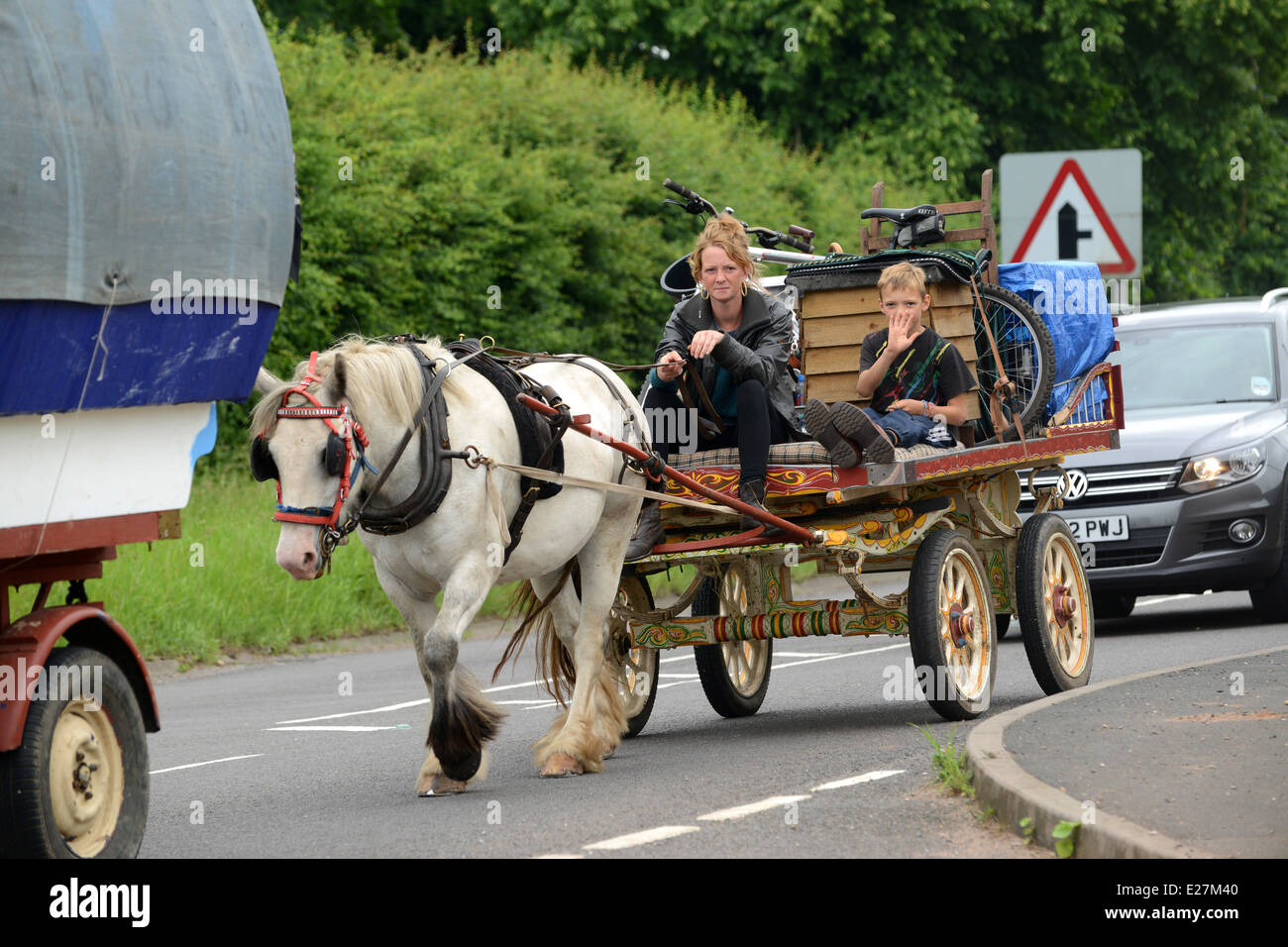 Travellers in horse drawn wagon cart travelling along busy road in West Midlands Uk  travellers wagon gypsy romany - Stock Image
