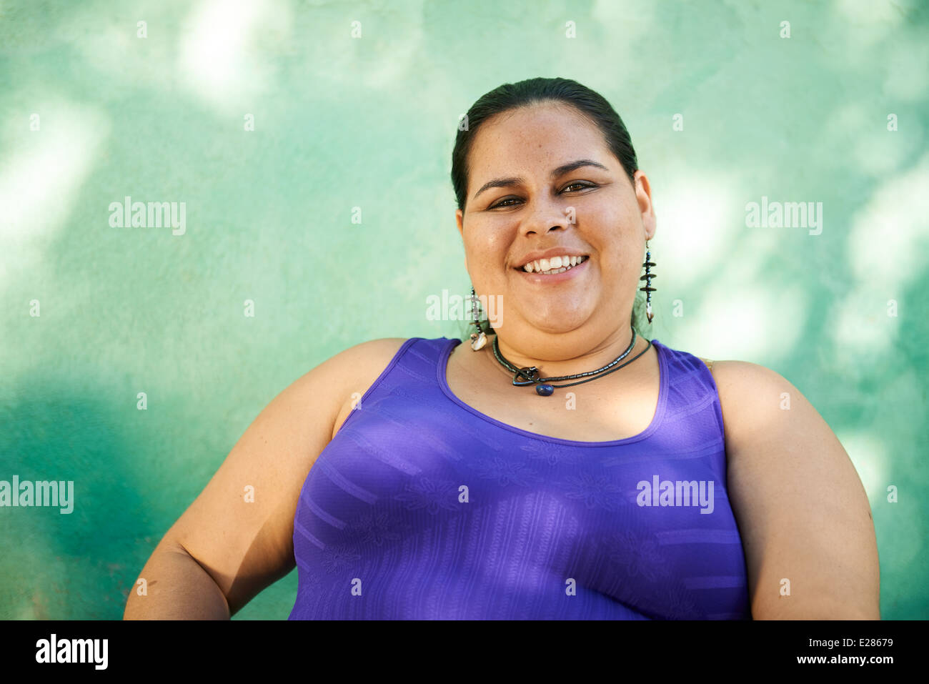 Portrait of overweight hispanic woman looking at camera and smiling - Stock Image