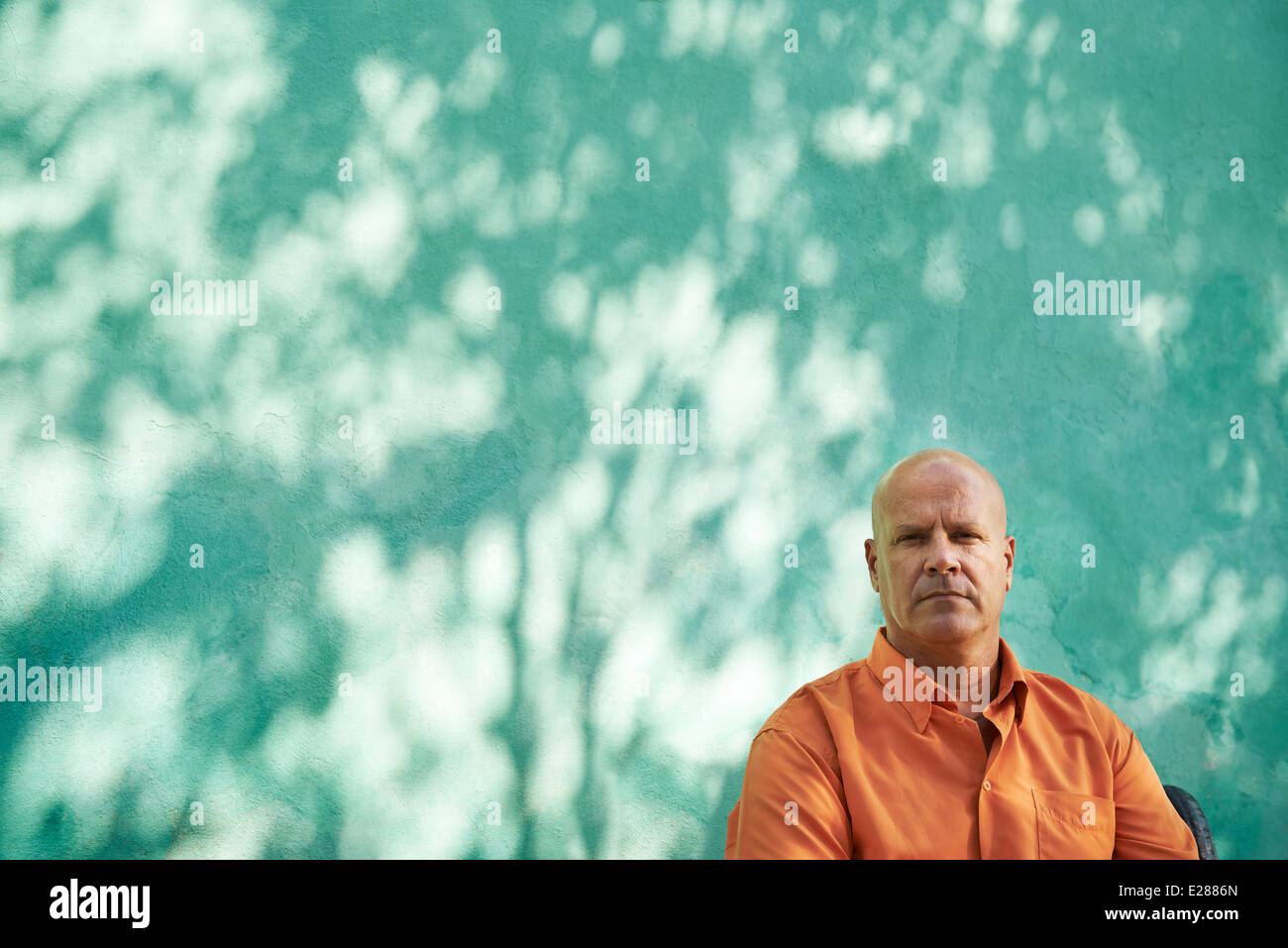 Portrait of mature caucasian man with orange shirt sitting in park and looking at camera with sad expression - Stock Image