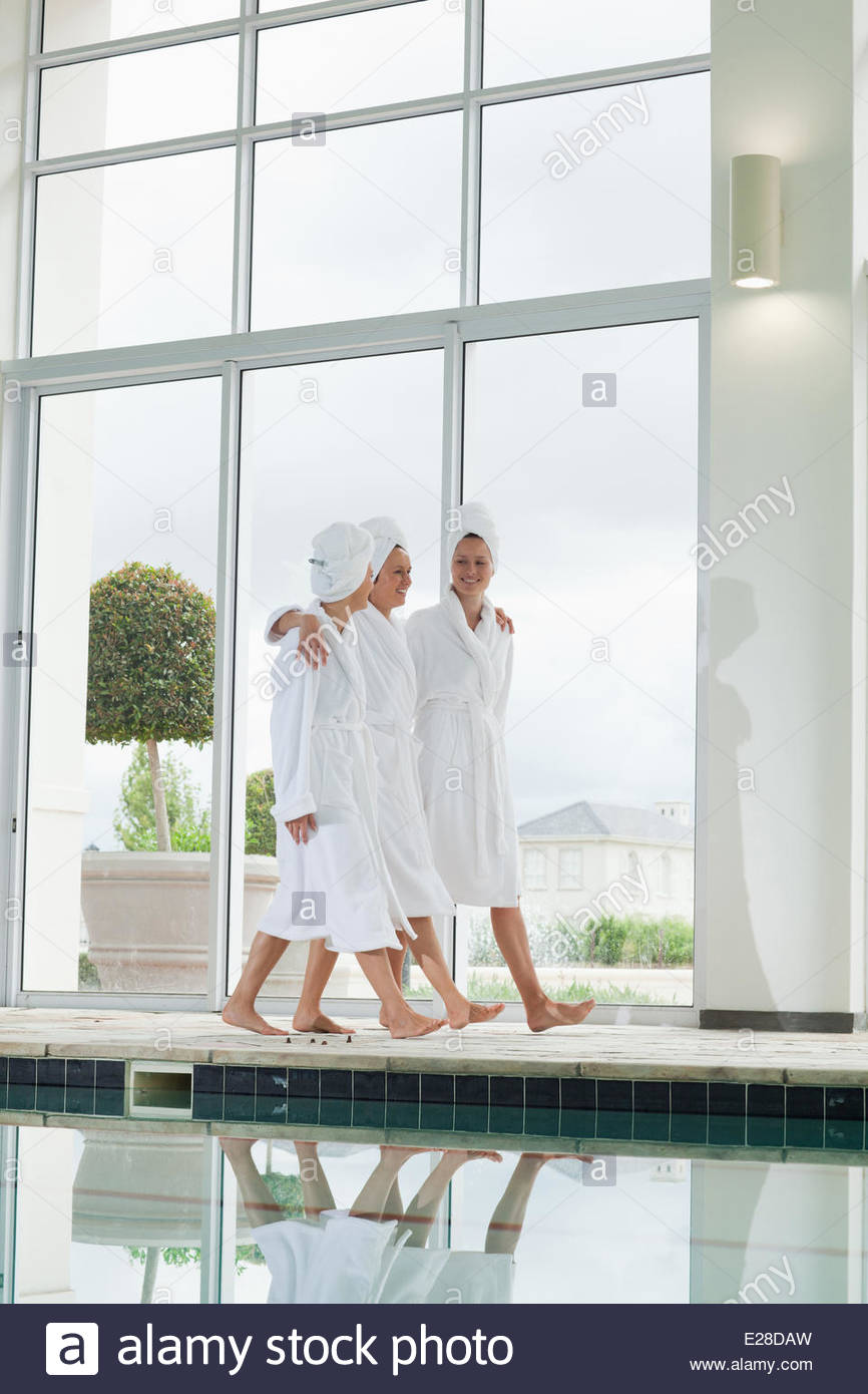 Women in bathrobes walking along swimming pool at spa Stock Photo