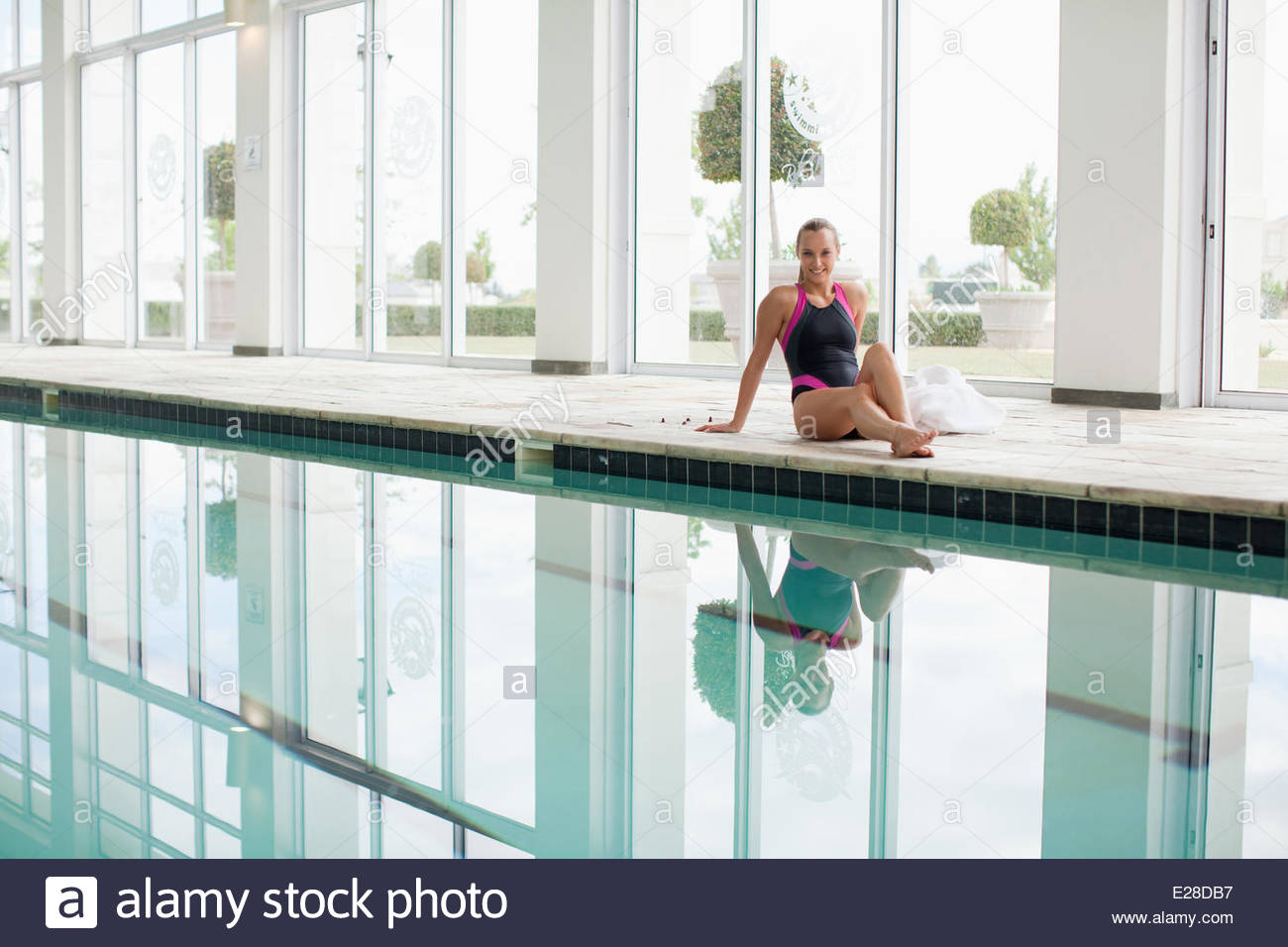 Portrait of smiling woman in bathing suit sitting poolside - Stock Image