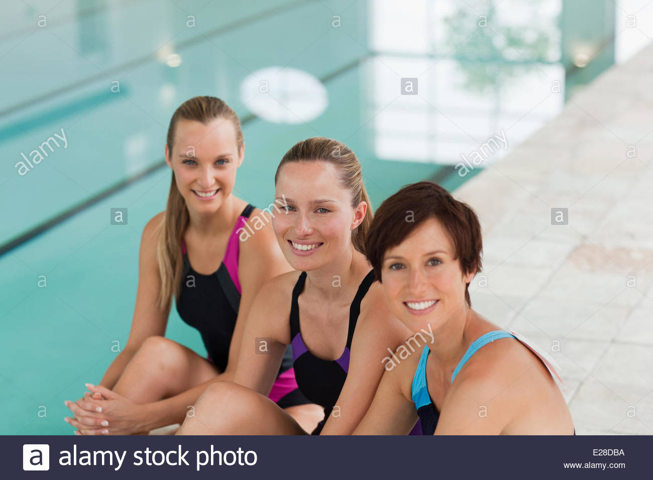 Smiling young women sitting at edge of swimming pool - Stock Image
