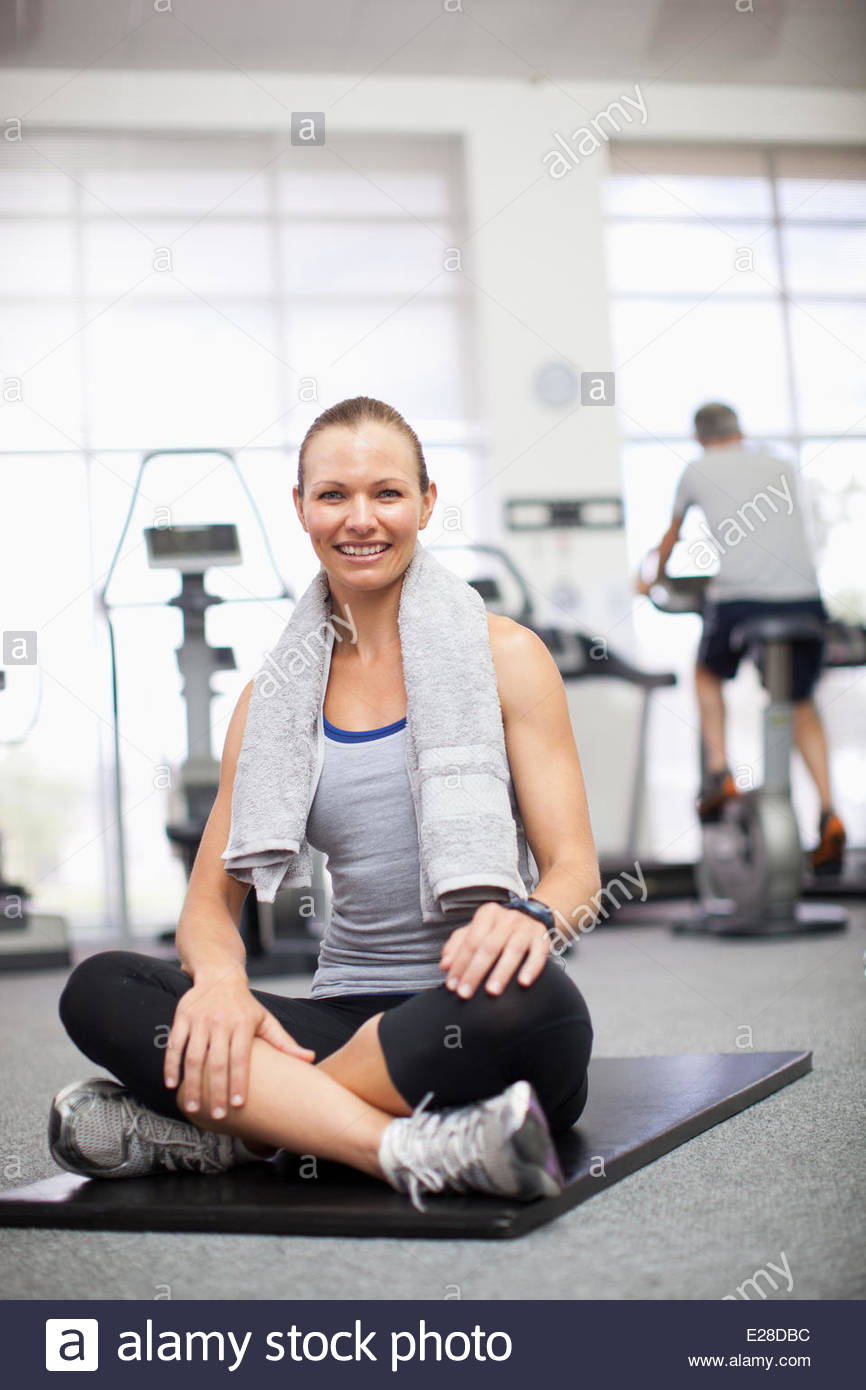 Portrait of smiling woman sitting on exercise mat in gymnasium - Stock Image
