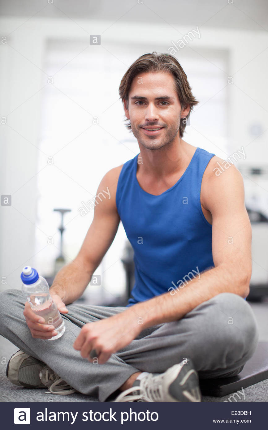 Portrait of smiling man sitting on exercise mat in gymnasium - Stock Image