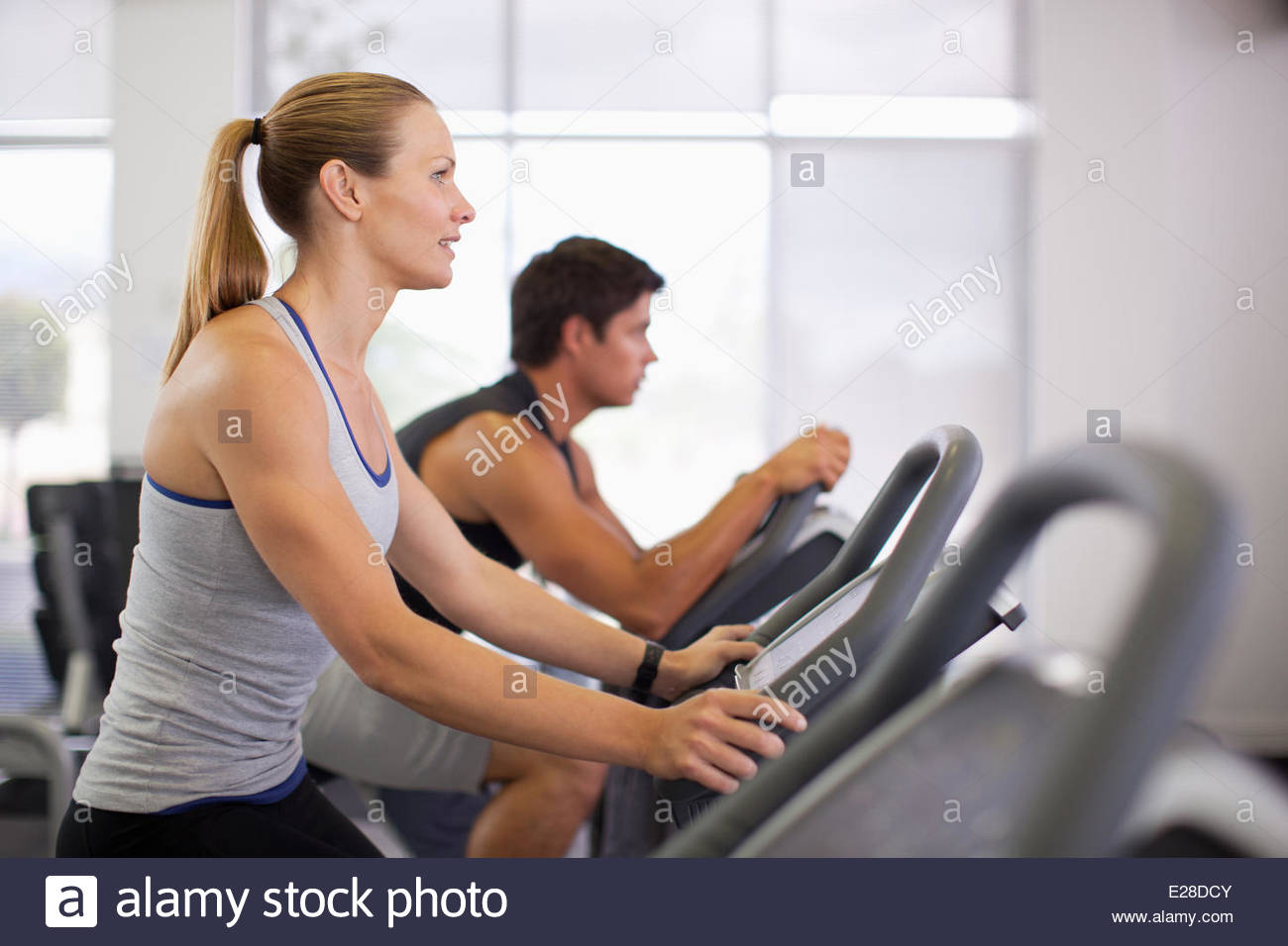Two people on exercise bikes in gymnasium - Stock Image
