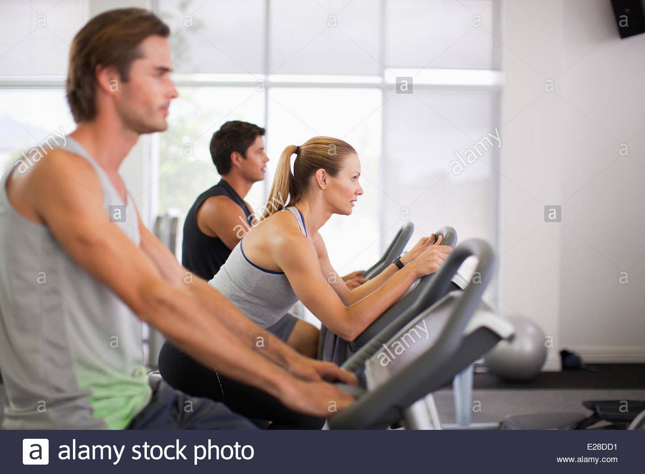 Three people on exercise bikes in gymnasium - Stock Image