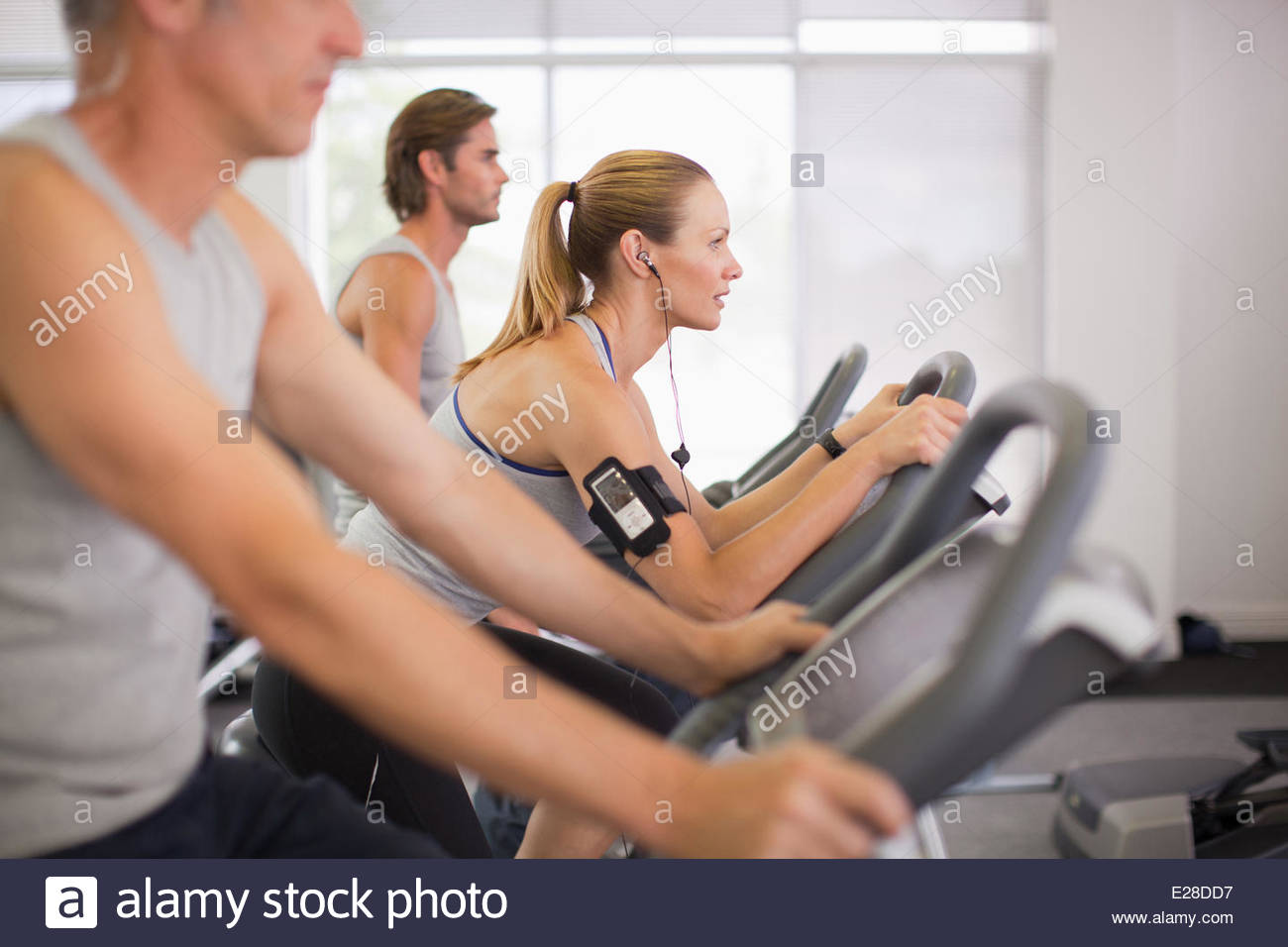 Three people on exercise bikes in gymnasium - Stock Image