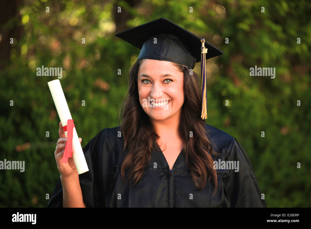 Attractive girl with blue eyes and brown hair wearing a graduation cap and gown and holding a diploma. - Stock Image