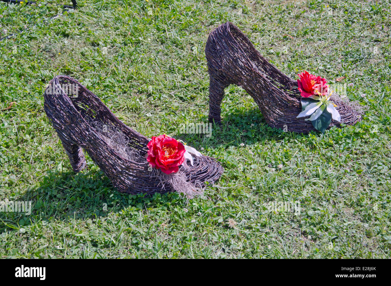 shoe stiletto wooden florist composition on grass in park - Stock Image