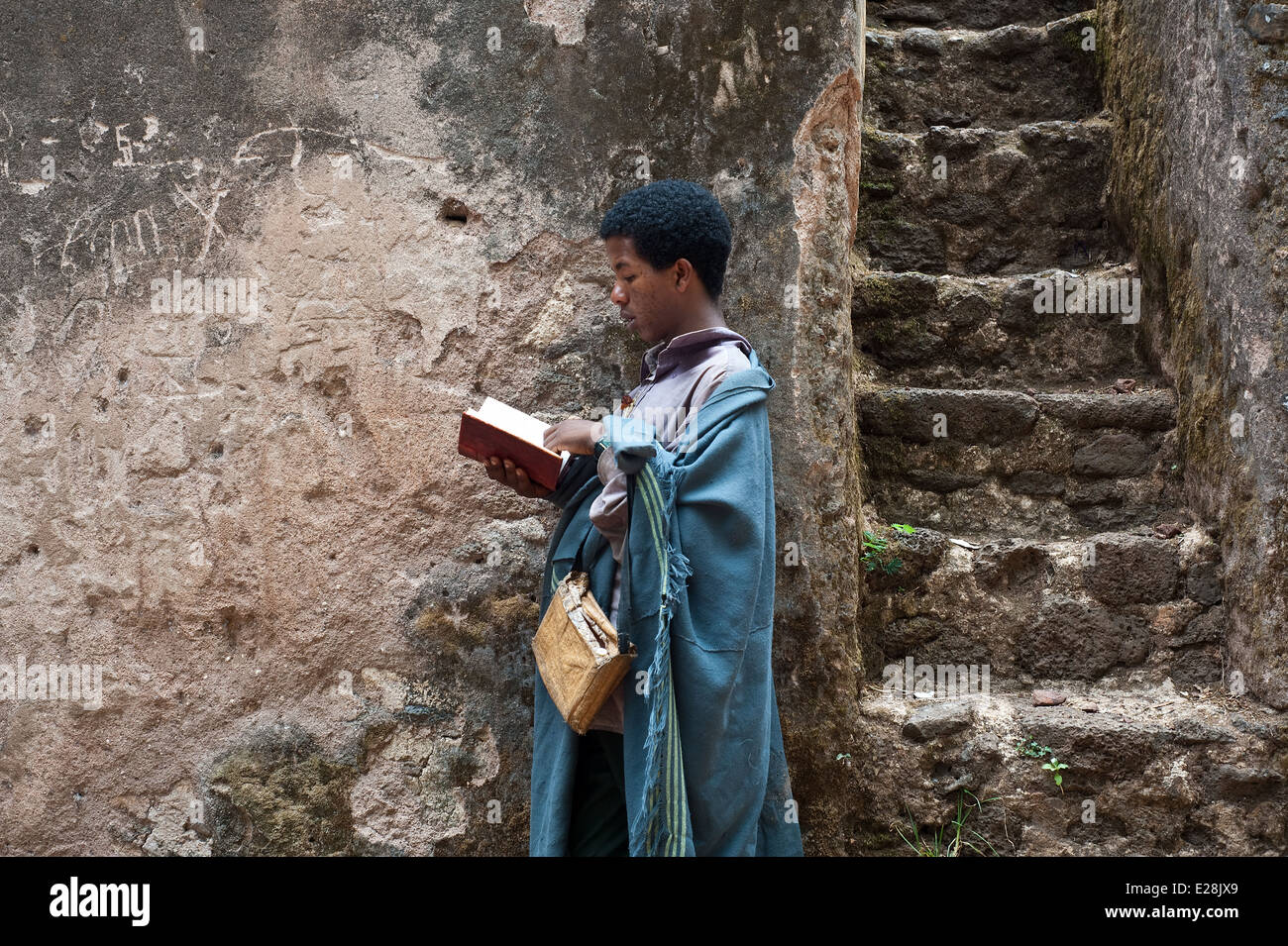 Orthodox christian boy reading the Bible during a mass ( Ethiopia) - Stock Image