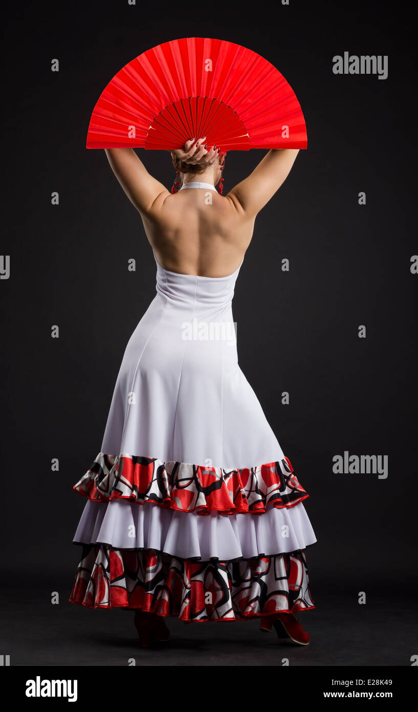 Flamenco dancer in white dress with big red fan standing back to camera - Stock Image