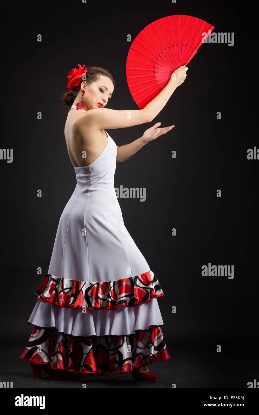 Flamenco dancer in white dress with big red fan - Stock Image