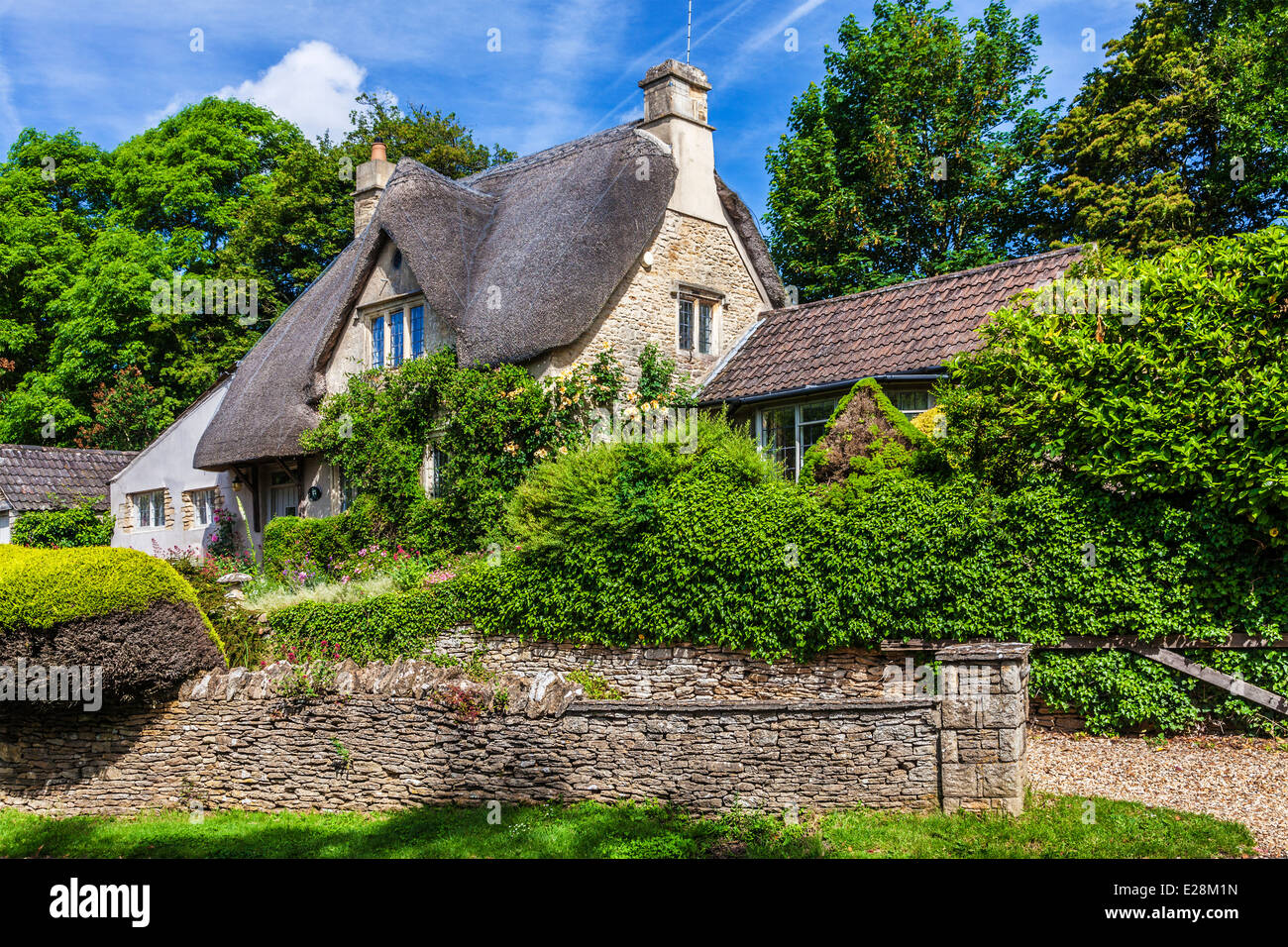 The picturesque thatched cottage in the Cotswold village of Castle Combe in Wiltshire. - Stock Image