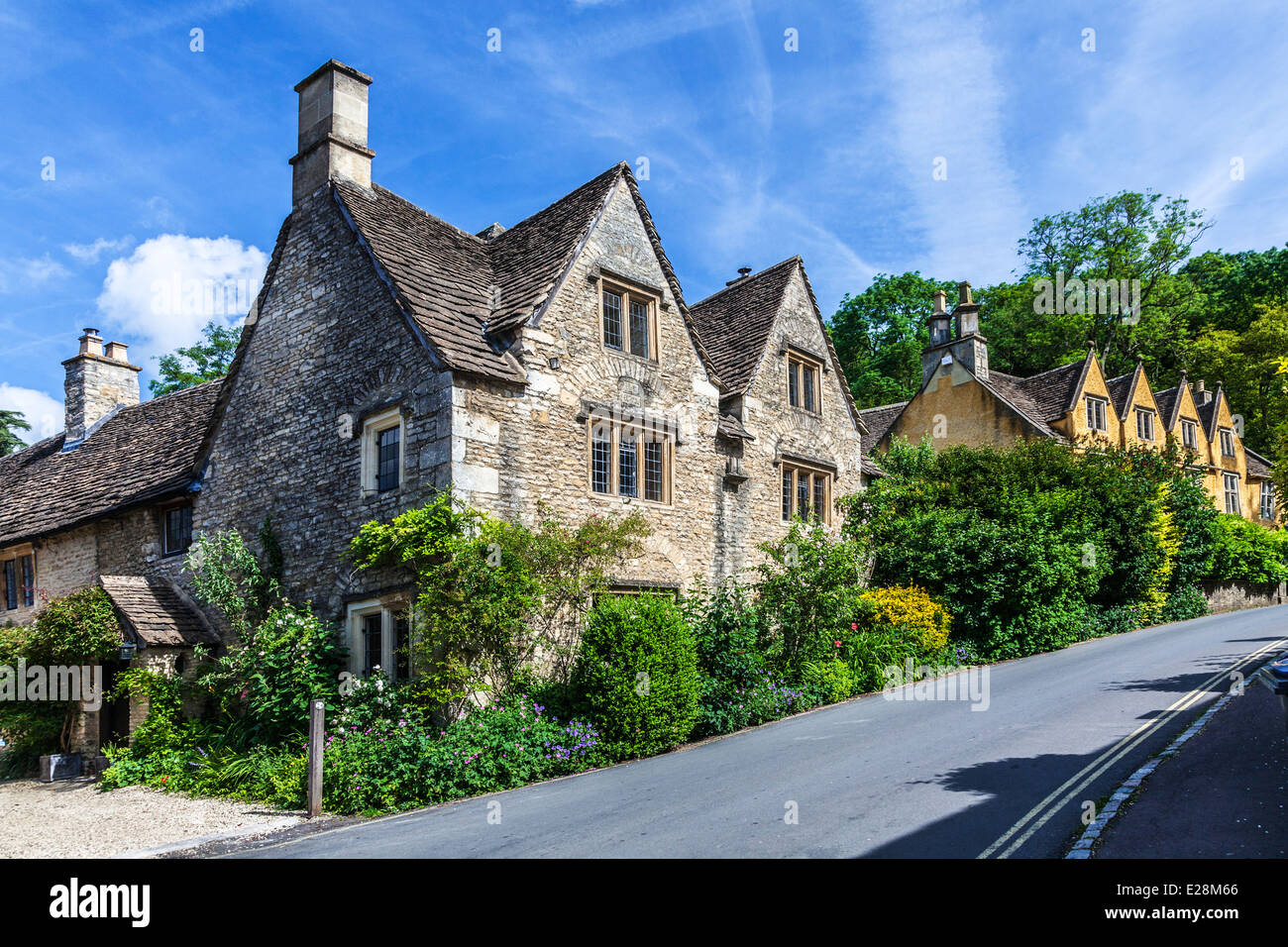 Roadside stone cottages in the Cotswold village of Castle Combe in Wiltshire. - Stock Image