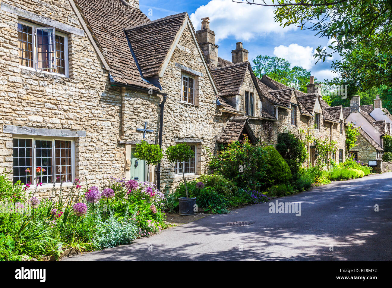 A lane of pretty terraced stone cottages in the Cotswold village of Castle Combe in Wiltshire. Stock Photo