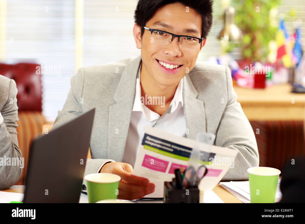 Happy asian businessman in glasses sitting at the table and holding document in office - Stock Image