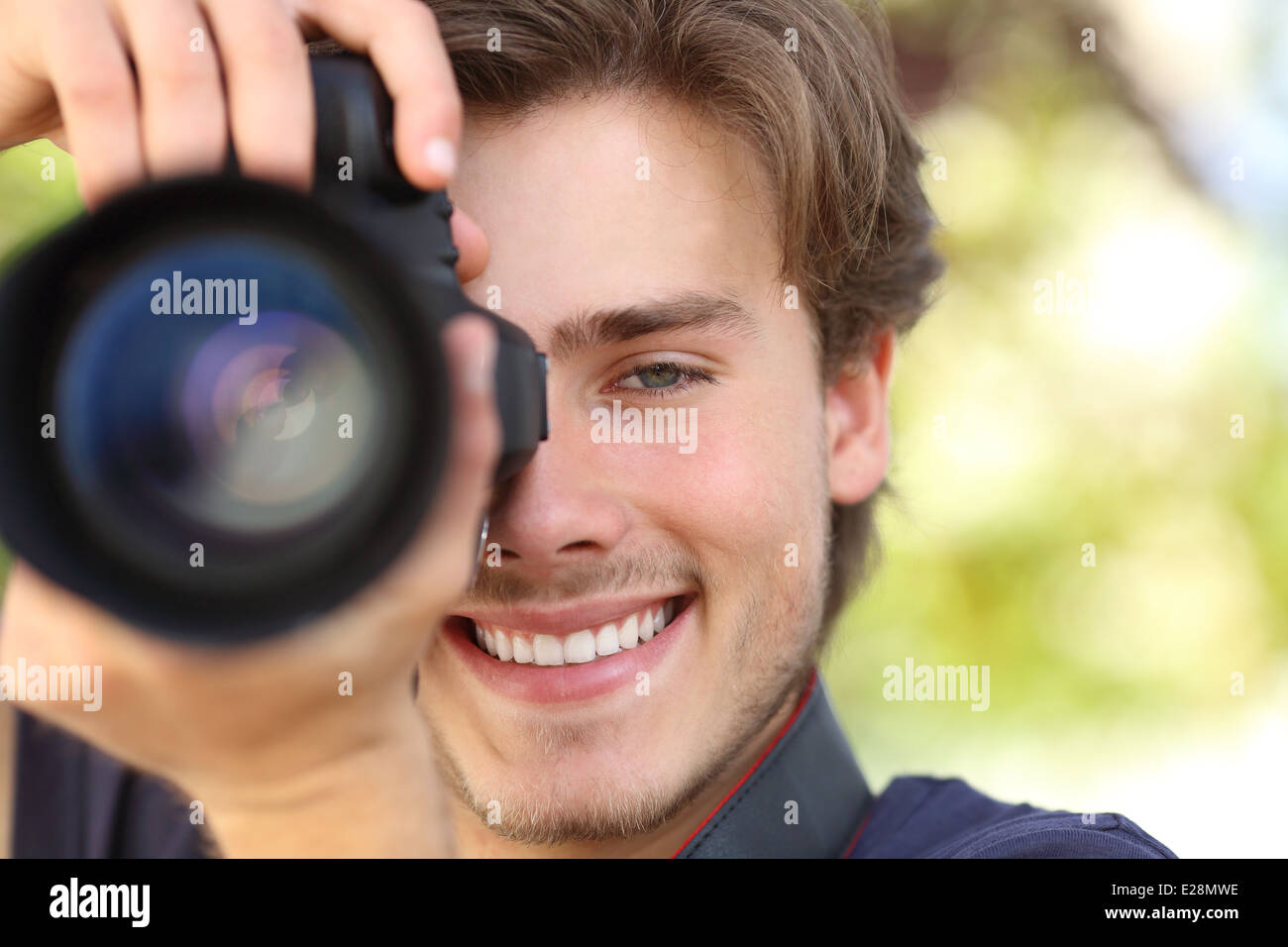 Front view of a photographer photographing with a dslr camera showing lens with a green background - Stock Image