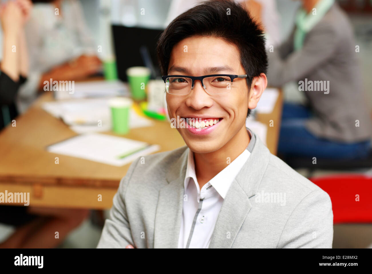 Portrait of happy businessman sitting in front of colleagues - Stock Image
