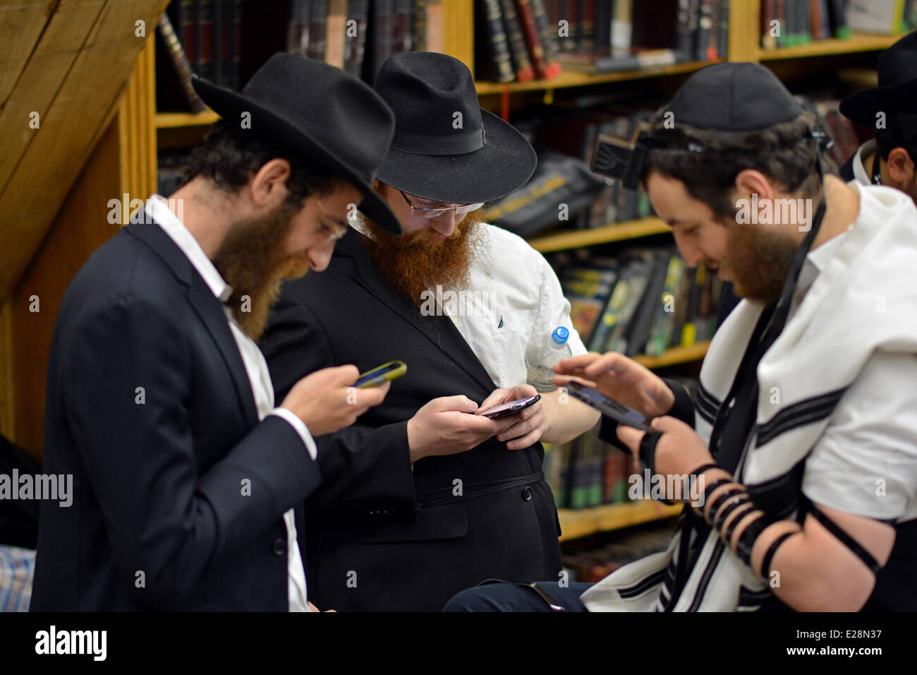 Three religious Jewish boys looking at their cell phones in the synagogue in Crown Heights, Brooklyn, New York - Stock Image