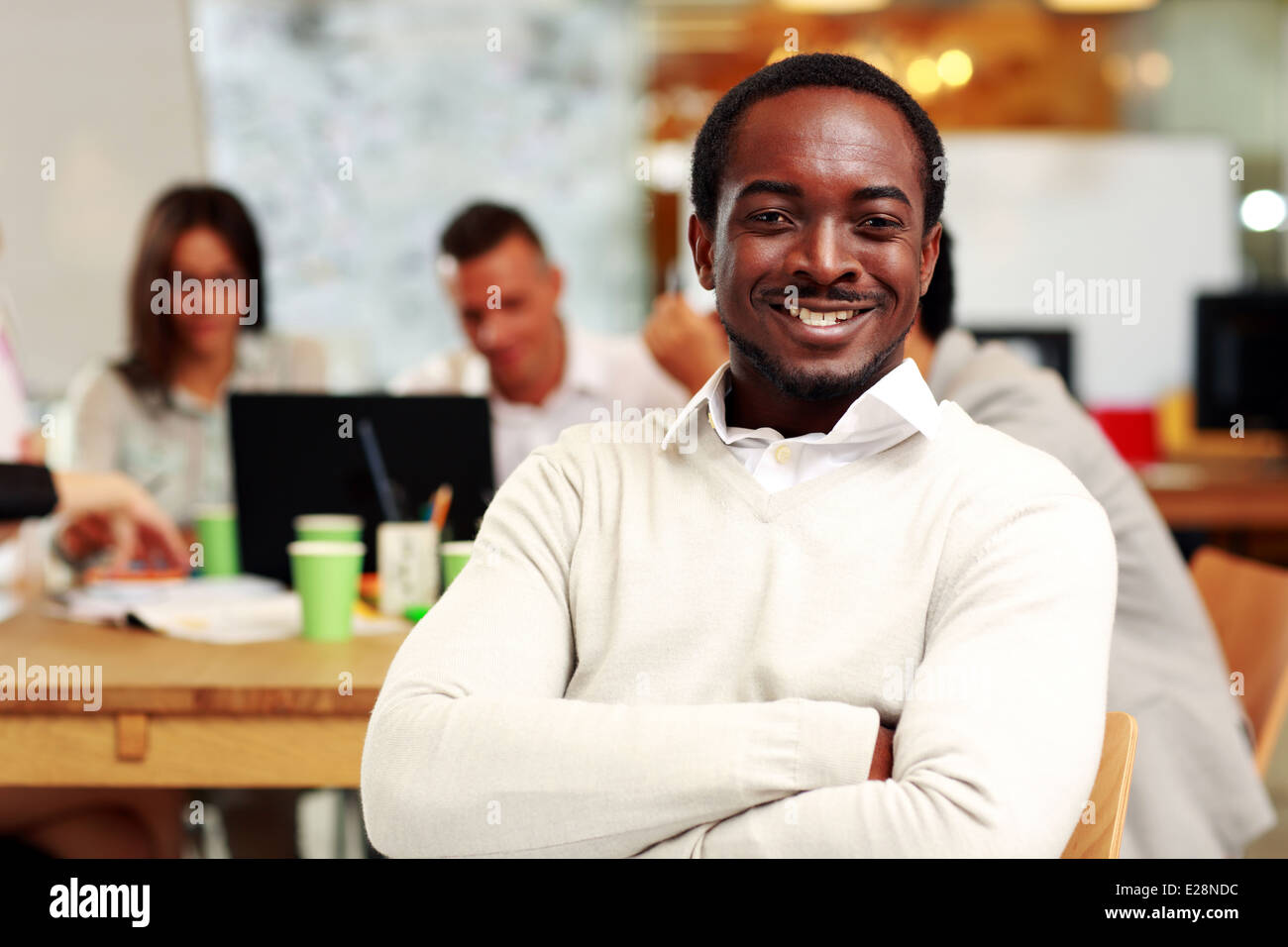 Portrait of a cheerful businessman sitting in front of colleagues - Stock Image