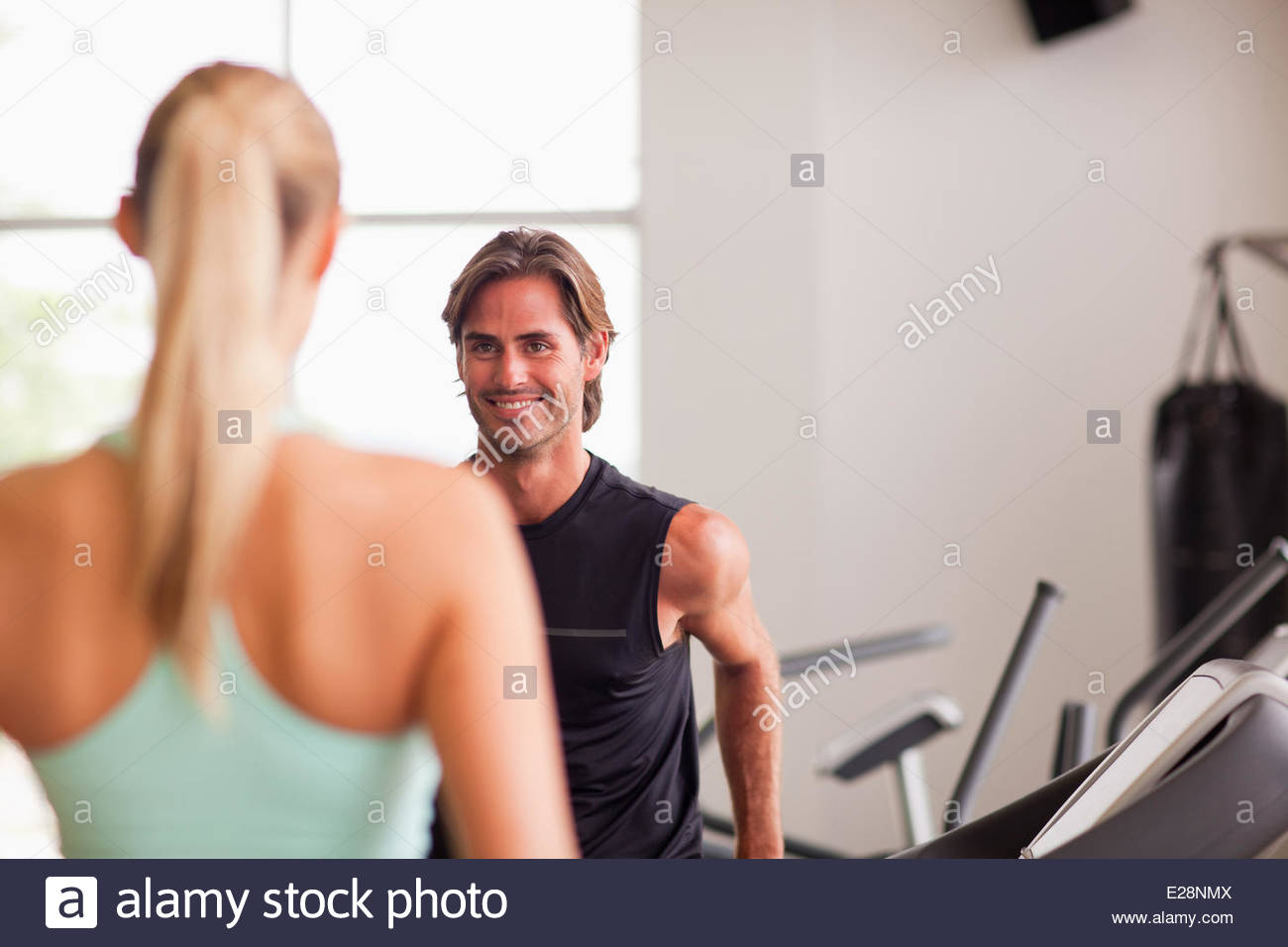 Man and woman talking on treadmills in gymnasium - Stock Image