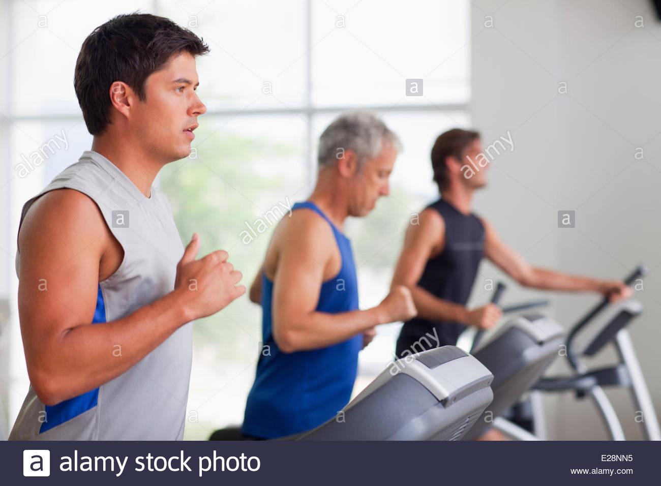 Men running on treadmills in gymnasium - Stock Image