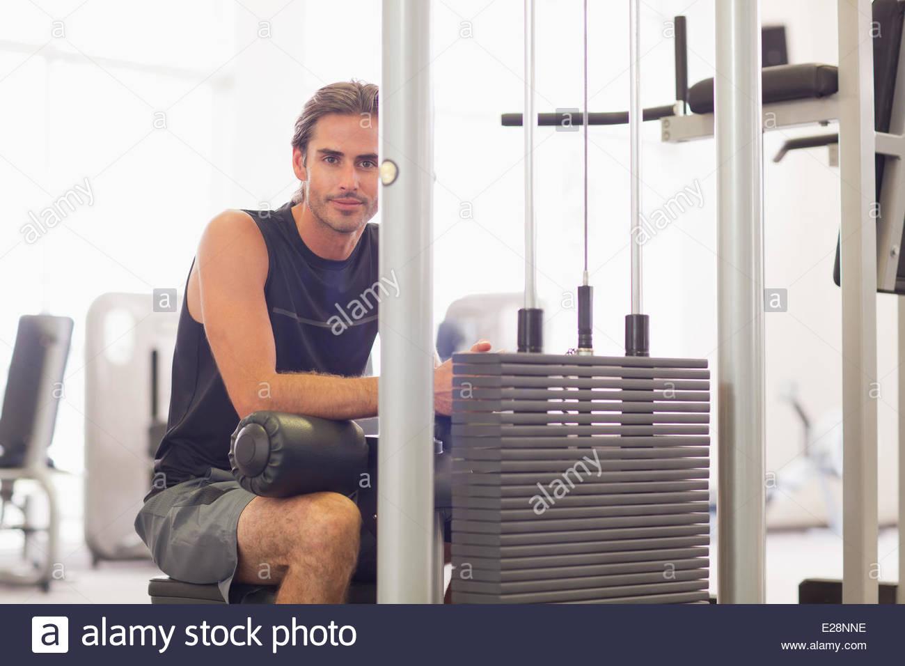 Portrait of smiling man using exercise equipment in gymnasium - Stock Image