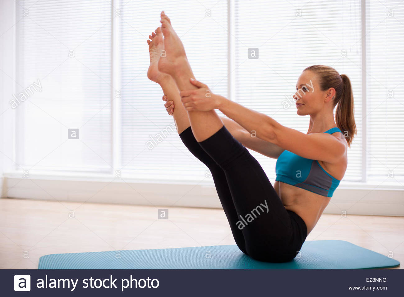 Woman stretching on yoga mat - Stock Image