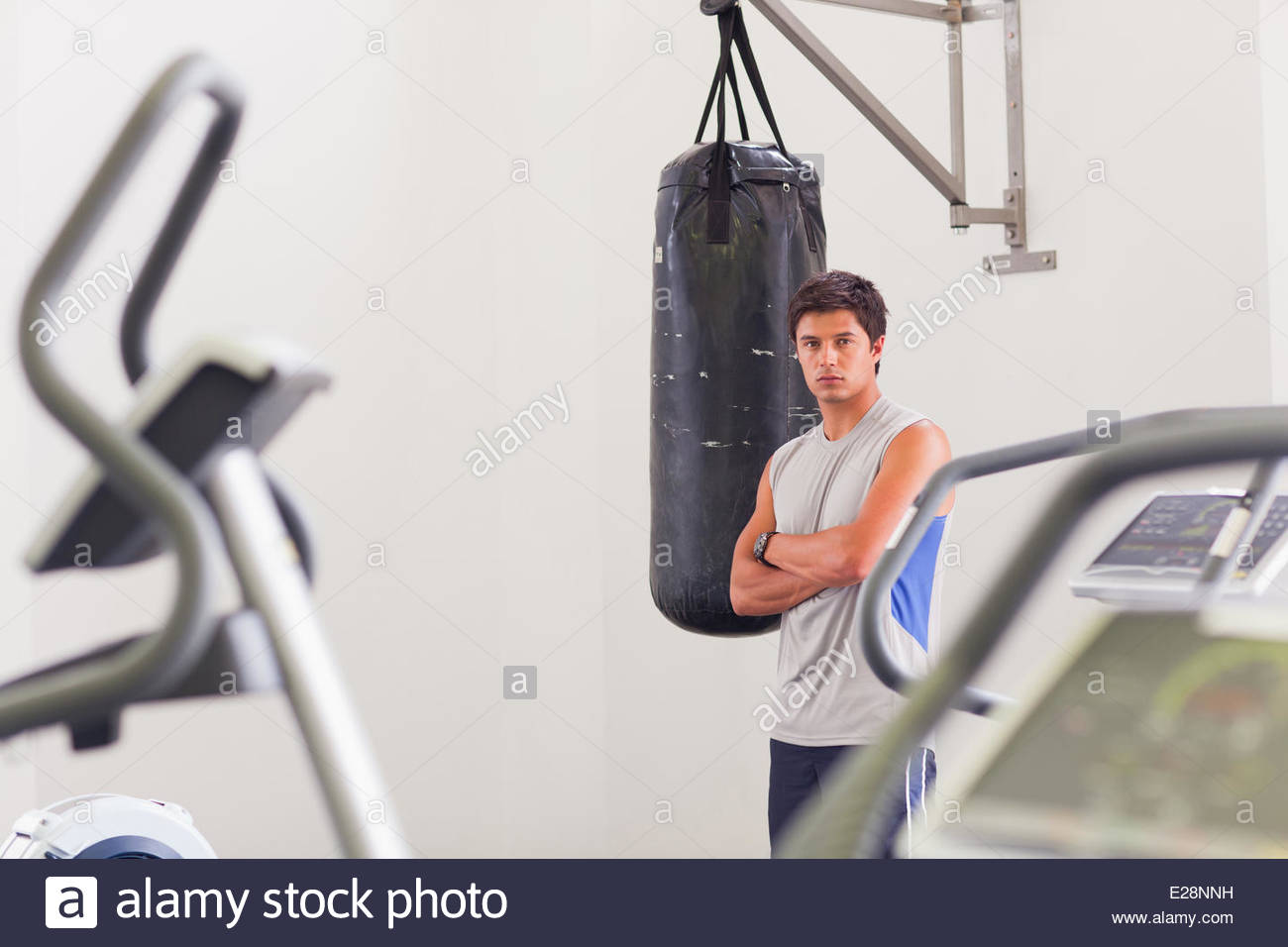 Portrait of man standing at punching bag in gymnasium - Stock Image