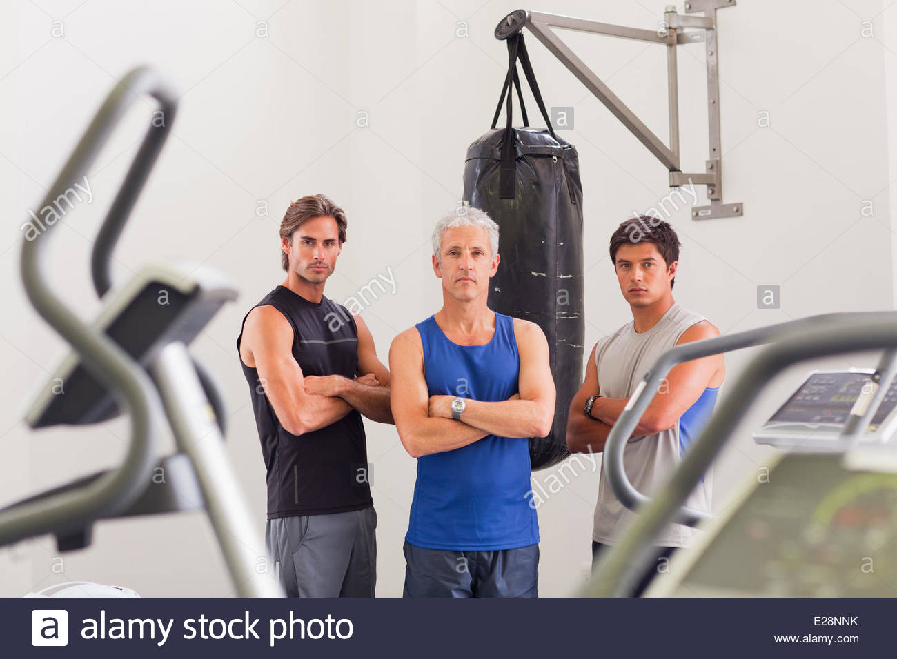 Portrait of smiling men with arms crossed near punching bag - Stock Image