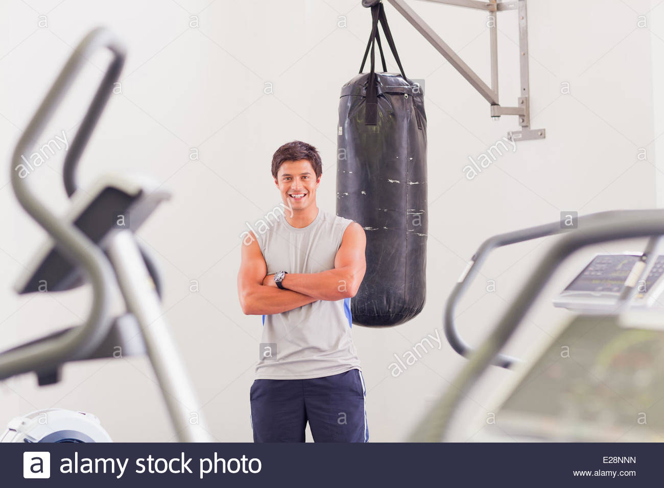 Portrait of smiling man standing at punching bag in gymnasium - Stock Image