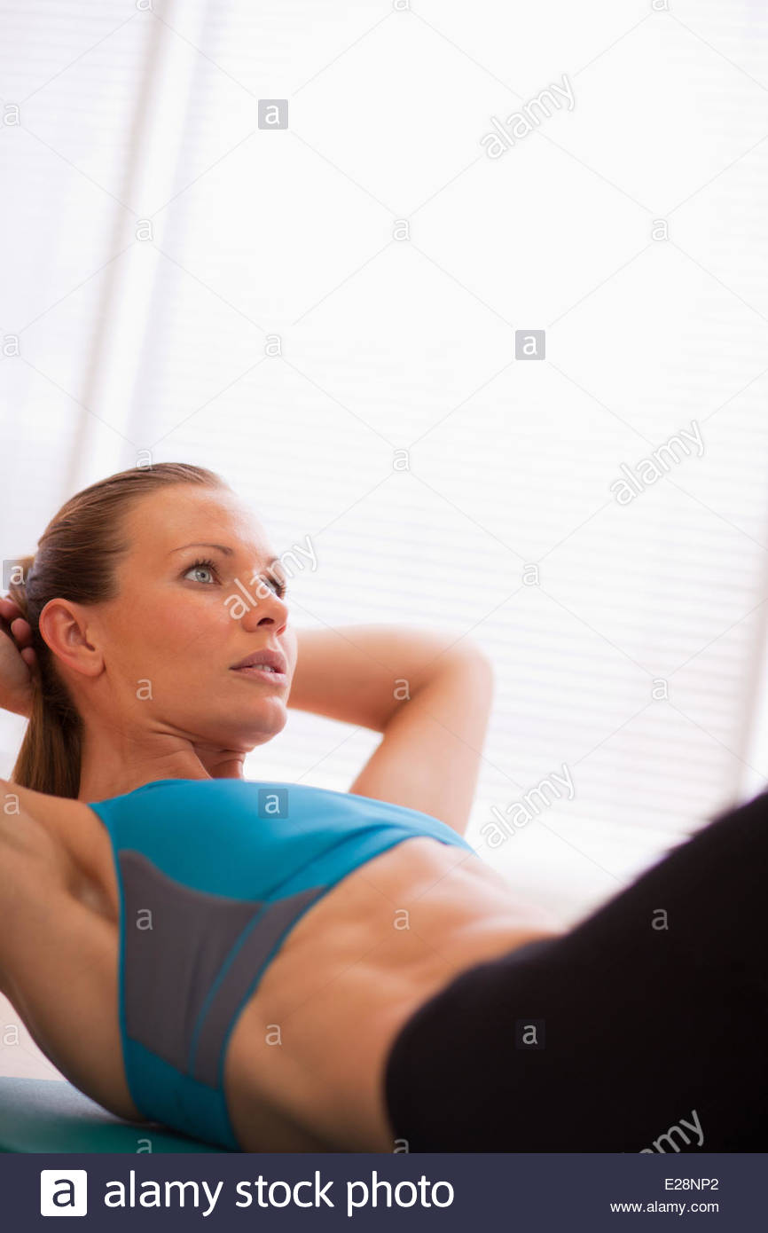 Serious woman in sports bra doing sit-ups on exercise mat - Stock Image