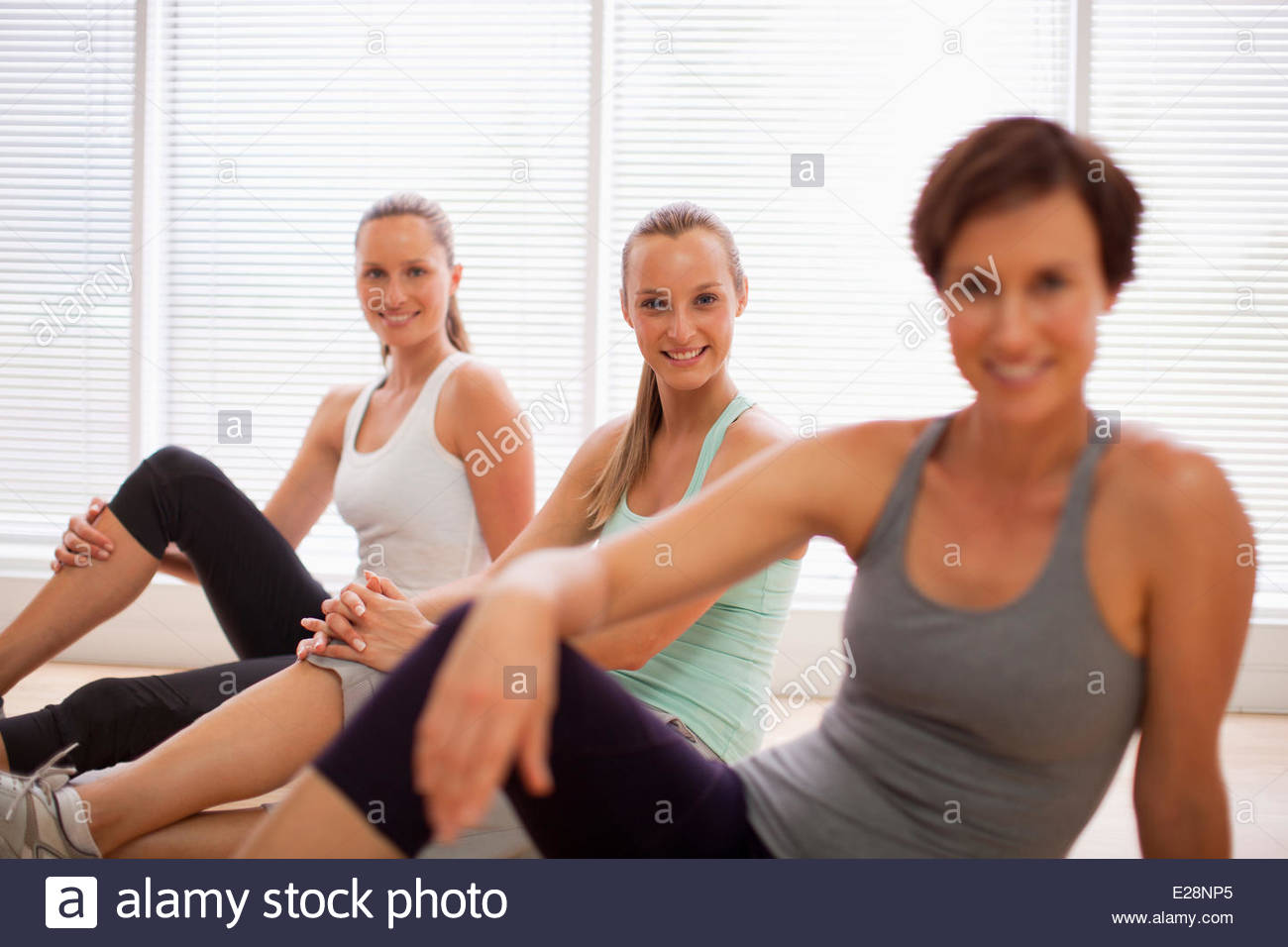 Portrait of smiling women sitting in a row in fitness studio - Stock Image