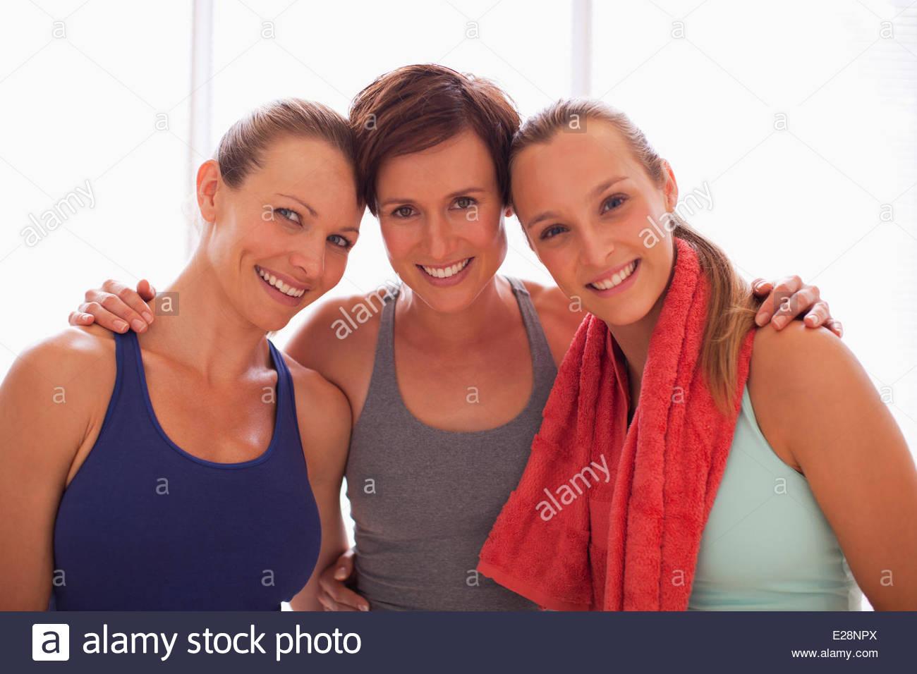 Portrait of smiling women hugging - Stock Image